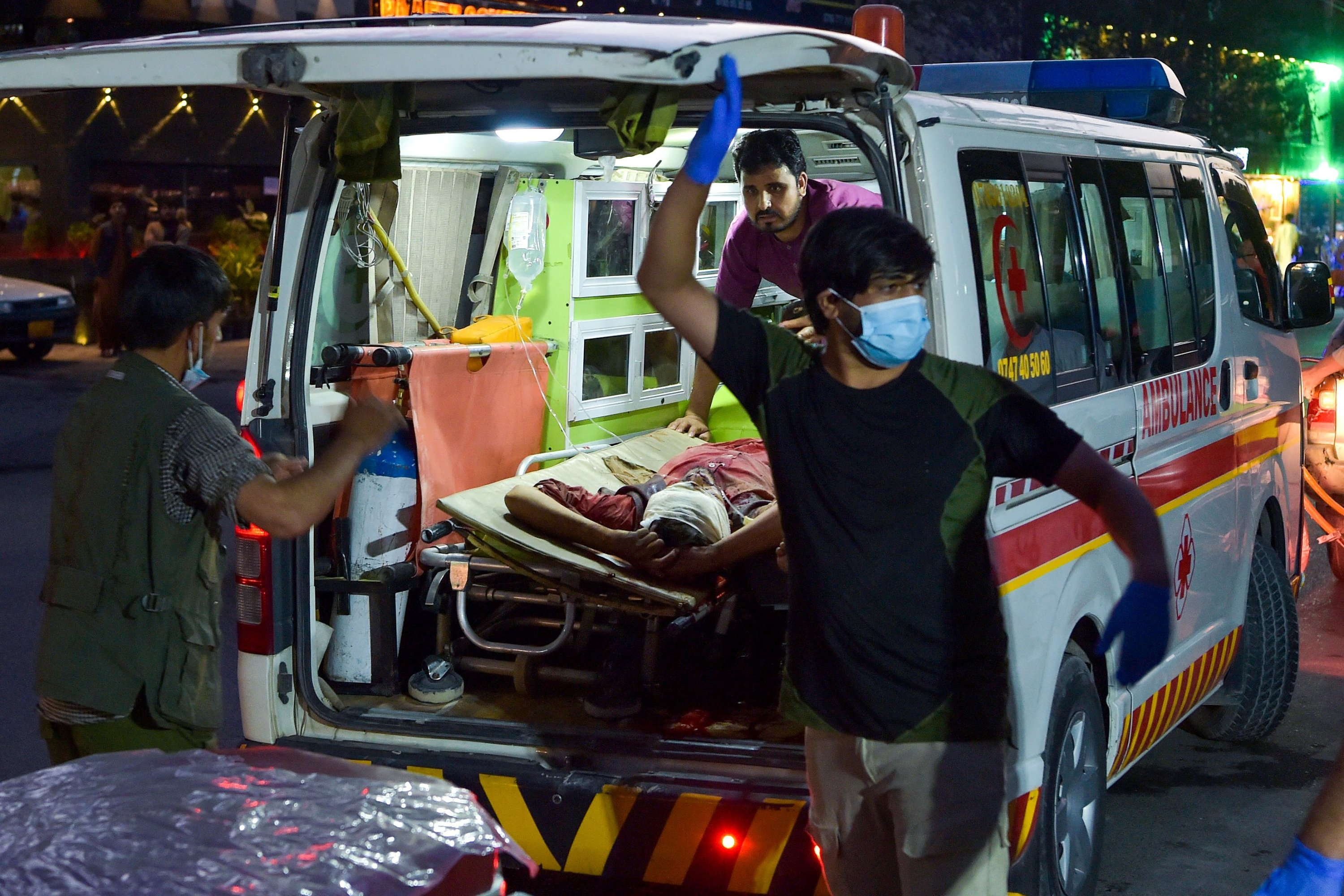 Medical staff bring an injured man to a hospital in an ambulance after two powerful explosions, which killed at least six people, outside the airport in Kabul, Afghanistan, Aug. 26, 2021. (Photo by Wakil KOHSAR via AFP)