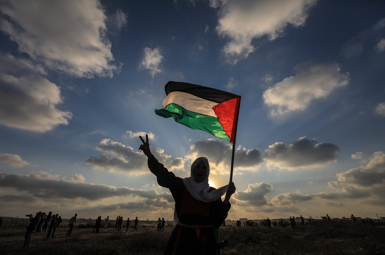 An elderly Palestinian woman holds up a Palestinian flag during a demonstration near the border between Israel and Gaza Strip, Aug. 21, 2021. (EPA Photo)