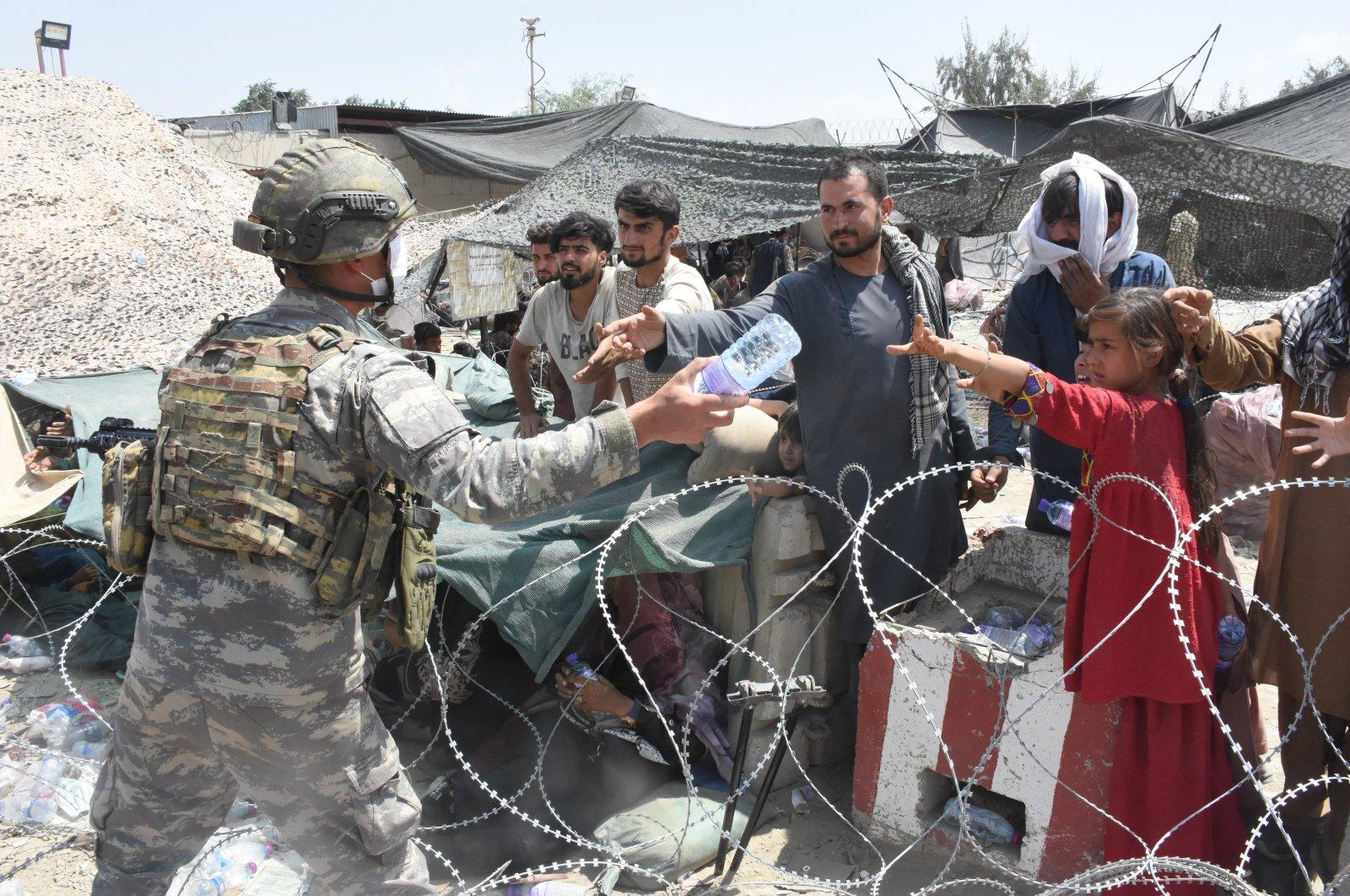 A Turkish soldier distributes water to Afghans waiting near Kabul Hamid Karzai International  Airport, Kabul, Afghanistan, Aug. 25, 2021. (AA Photo)
