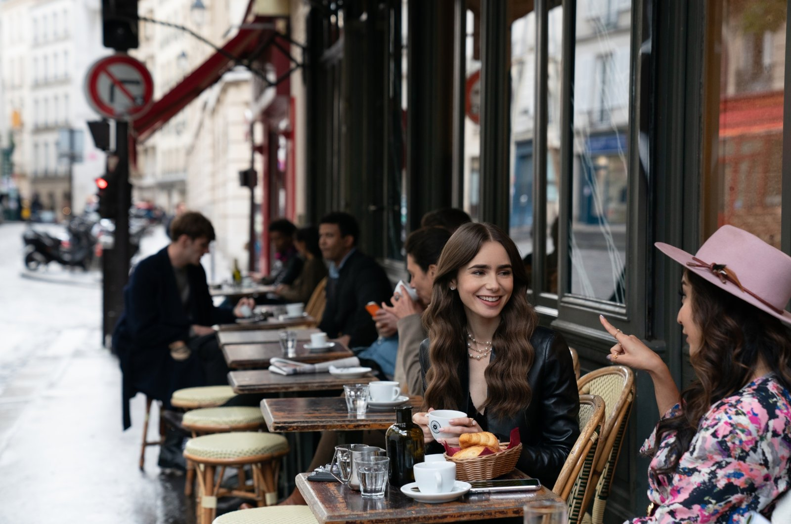 """Emily, played by Lily Collins, sits with a friend in a Parisian cafe in the first season of the Netflix series """"Emily in Paris."""" (DPA Photo)"""