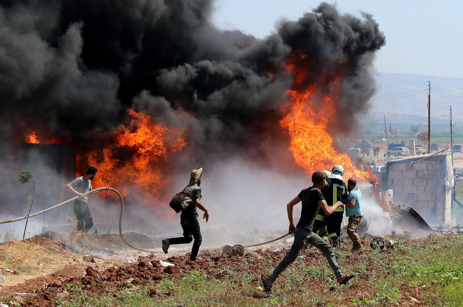 Civilians and members of the White Helmets rush to put out a fire caused by reported artillery bombardment by Syrian regime forces in northern Afrin, Syria, Aug. 18, 2021. (AFP Photo)