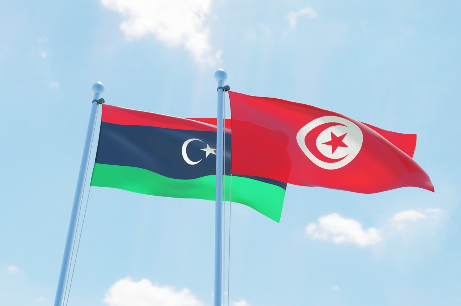 Tunisian and Libyan flags waving against a blue sky. (Shutterstock Photo)