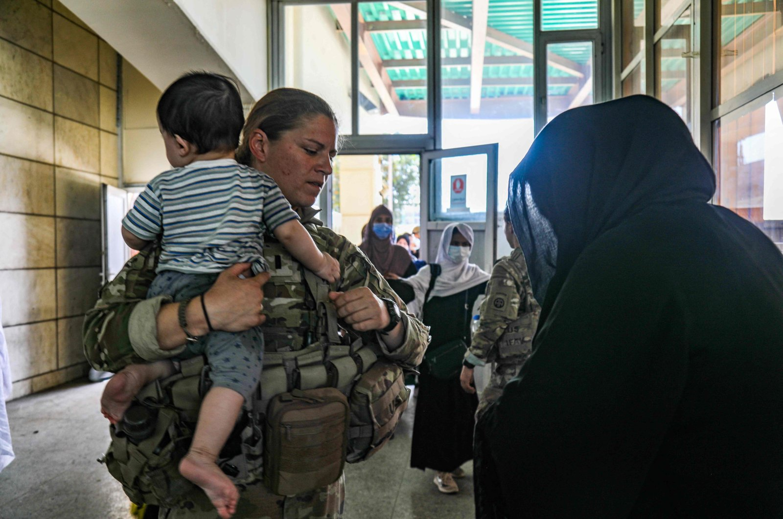 A medical officer assigned to the 82nd Airborne Division speaks with an Afghan woman and helps her with her child as part of the ongoing noncombatant evacuation of U.S. civilian personnel, Special Immigrant Visa applicants, and other at-risk individuals from Afghanistan from Hamid Karzai International Airport in Kabul, Afghanistan, Aug. 25, 2021. (AFP Photo)