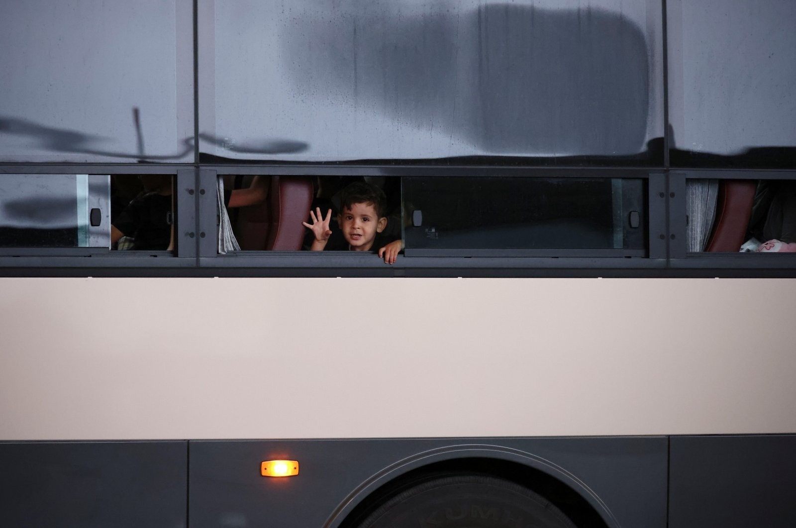 An Afghan boy waves as he leaves Incheon International Airport after arriving in South Korea with other Afghan evacuees who supported the South Korean government's activities in Afghanistan, in Incheon, South Korea, Aug. 26, 2021. (Reuters Photo)