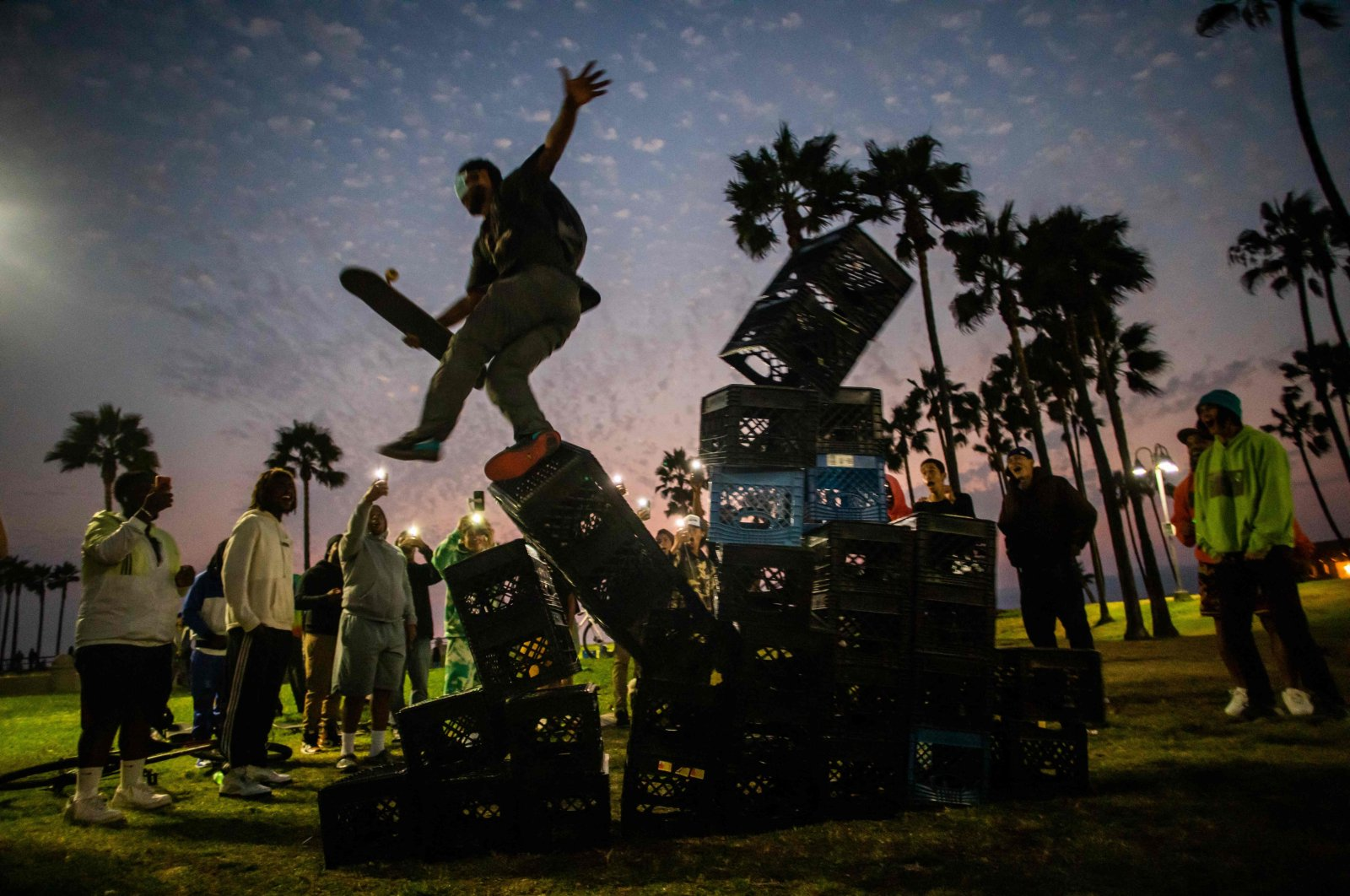A man falls down from a pyramid of milk crates while he participates in the milk crate challenge, in Venice, California, U.S., Aug. 24, 2021. (AFP Photo)