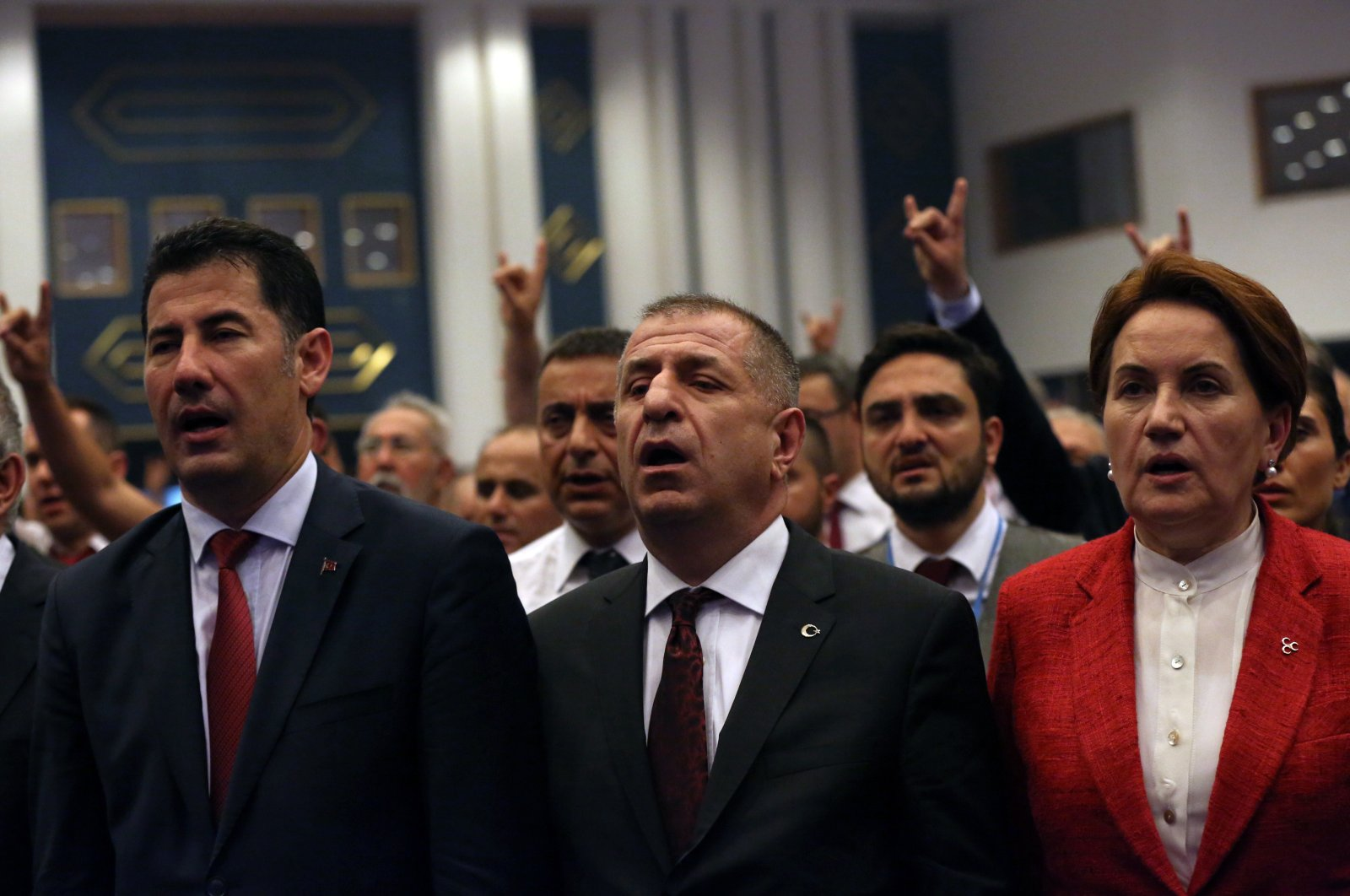 Candidates for the leadership of the Nationalist Movement Party (MHP), Ümit Özdağ (C), Meral Aksener (R), who is now IP chairperson, and Sinan Ogan sing the national anthem during an MHP congress outside Ankara, Turkey, June 19, 2016. (AP Photo)
