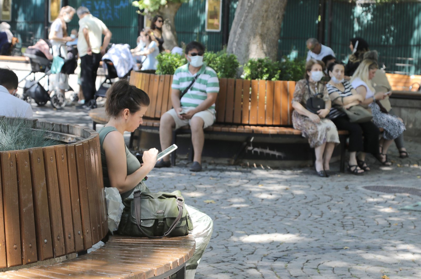 A woman checks her tablet computer at a park in Çankaya district, in the capital Ankara, Turkey, Aug. 26, 2021. (IHA Photo)
