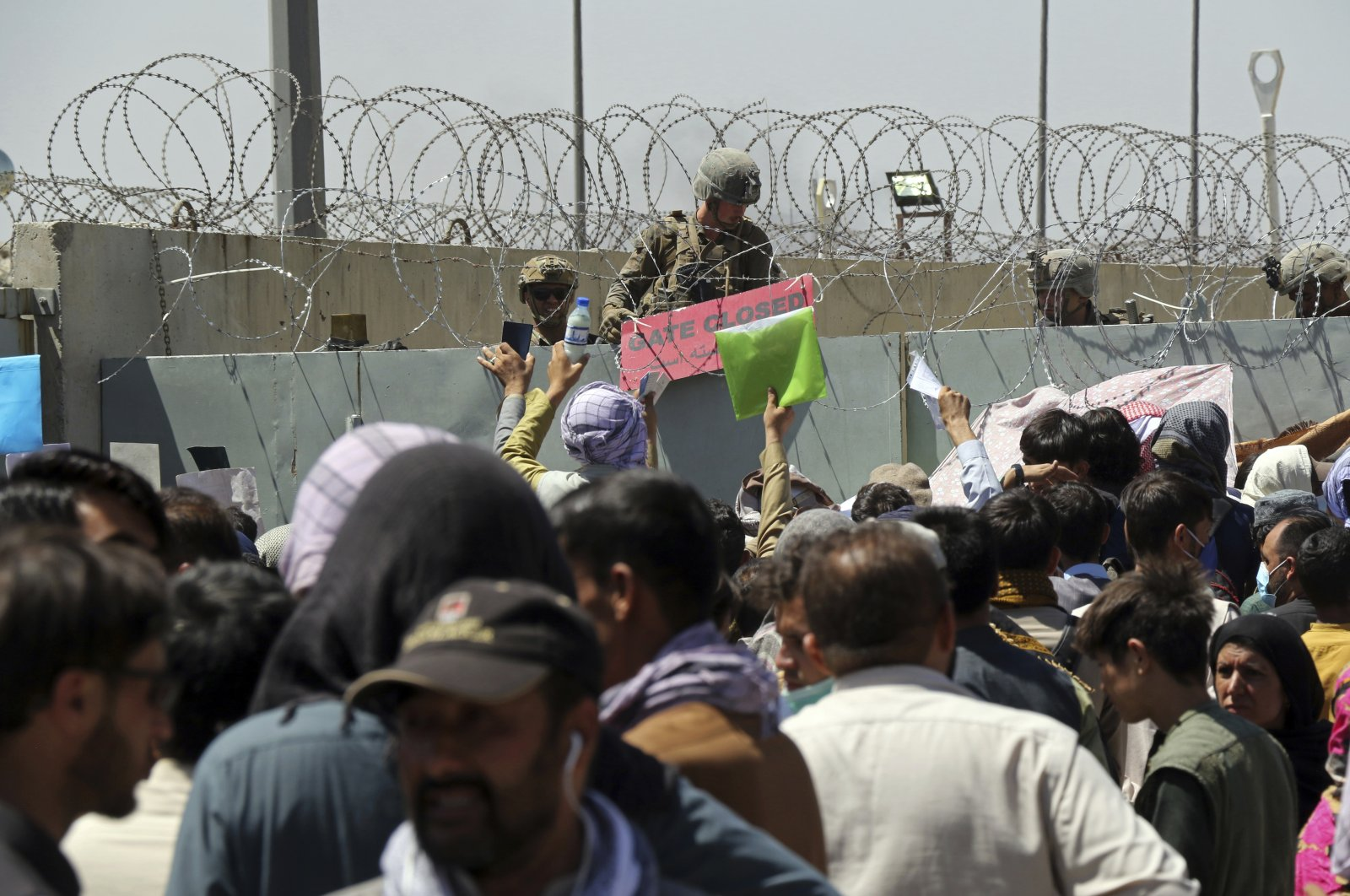 A U.S. soldier holds a sign indicating a gate is closed as hundreds of people gather, some holding documents, near an evacuation control checkpoint on the perimeter of Hamid Karzai International Airport, in Kabul, Afghanistan, Aug. 26, 2021. (AP Photo)
