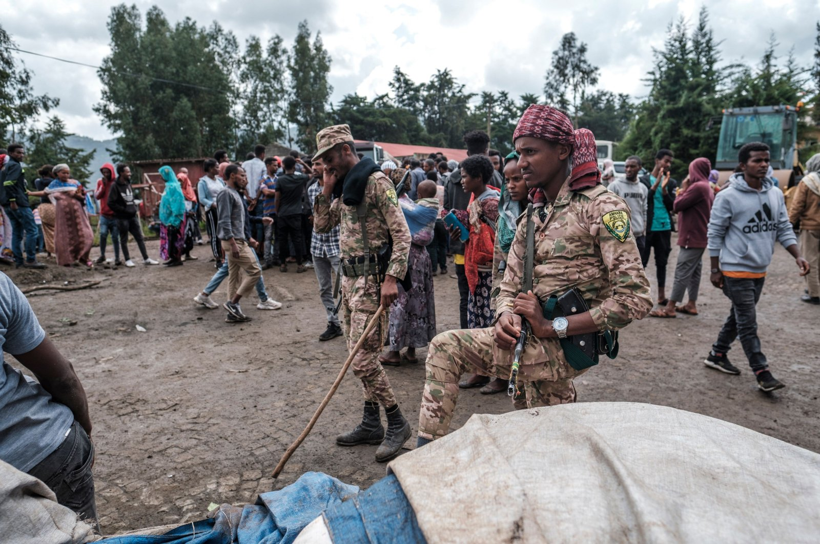 Members of the Special Force of the Amhara Police stand next to sacks of food during a food distribution for internally displaced people (IDP) from the Amhara region, in the city of Dessie, Ethiopia, Aug. 23, 2021. (Photo by Eduardo Soteras via AFP Photo)