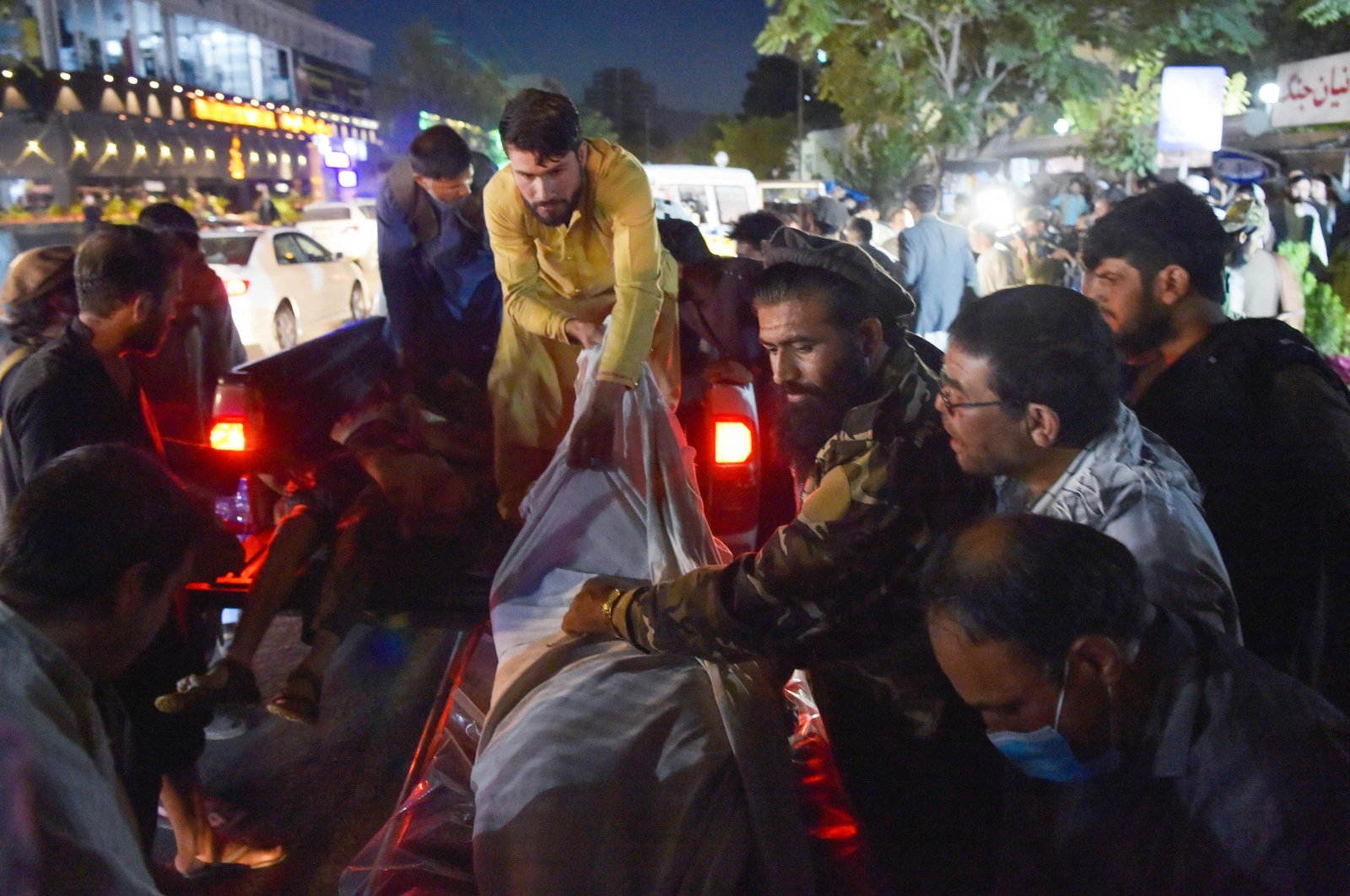 Volunteers and medical staff unload bodies from a pickup truck outside a hospital after two powerful explosions, which killed at least six people, outside the airport in Kabul, Afghanistan, Aug. 26, 2021. (Photo by Wakil KOHSAR via AFP)