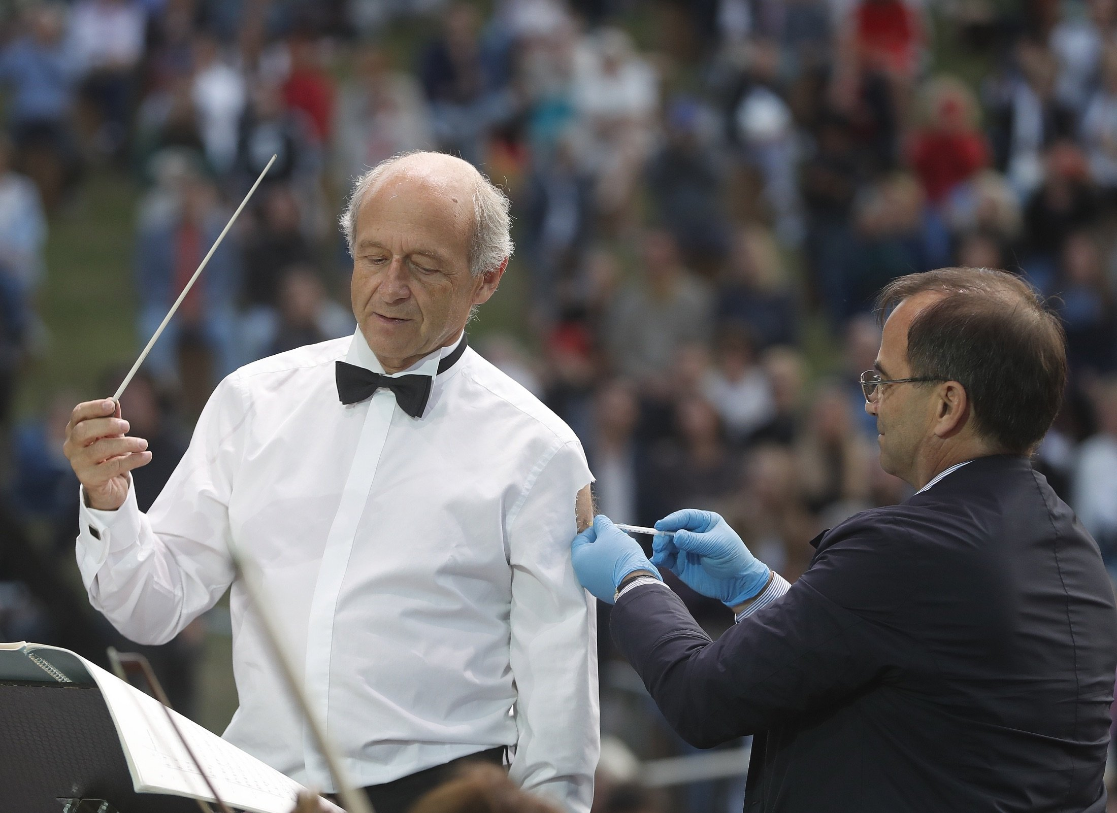Ivan Fischer, the founder of the Budapest Festival Orchestra, receives his third dose of the COVID-19 vaccine as he conducts the orchestra, during a free concert in Budapest, Hungary, Aug. 25, 2021. (AP Photo)