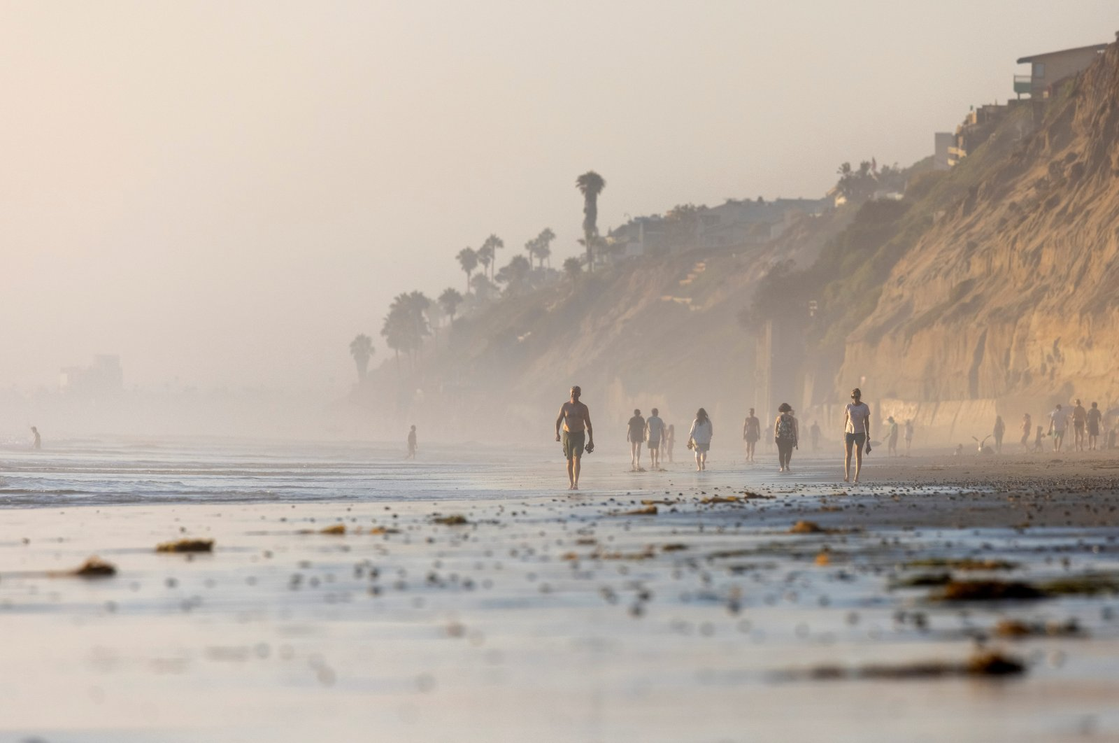 People cool off with an evening walk along the beach in Encinitas, California, U.S., Aug. 26, 2021. (Reuters Photo)