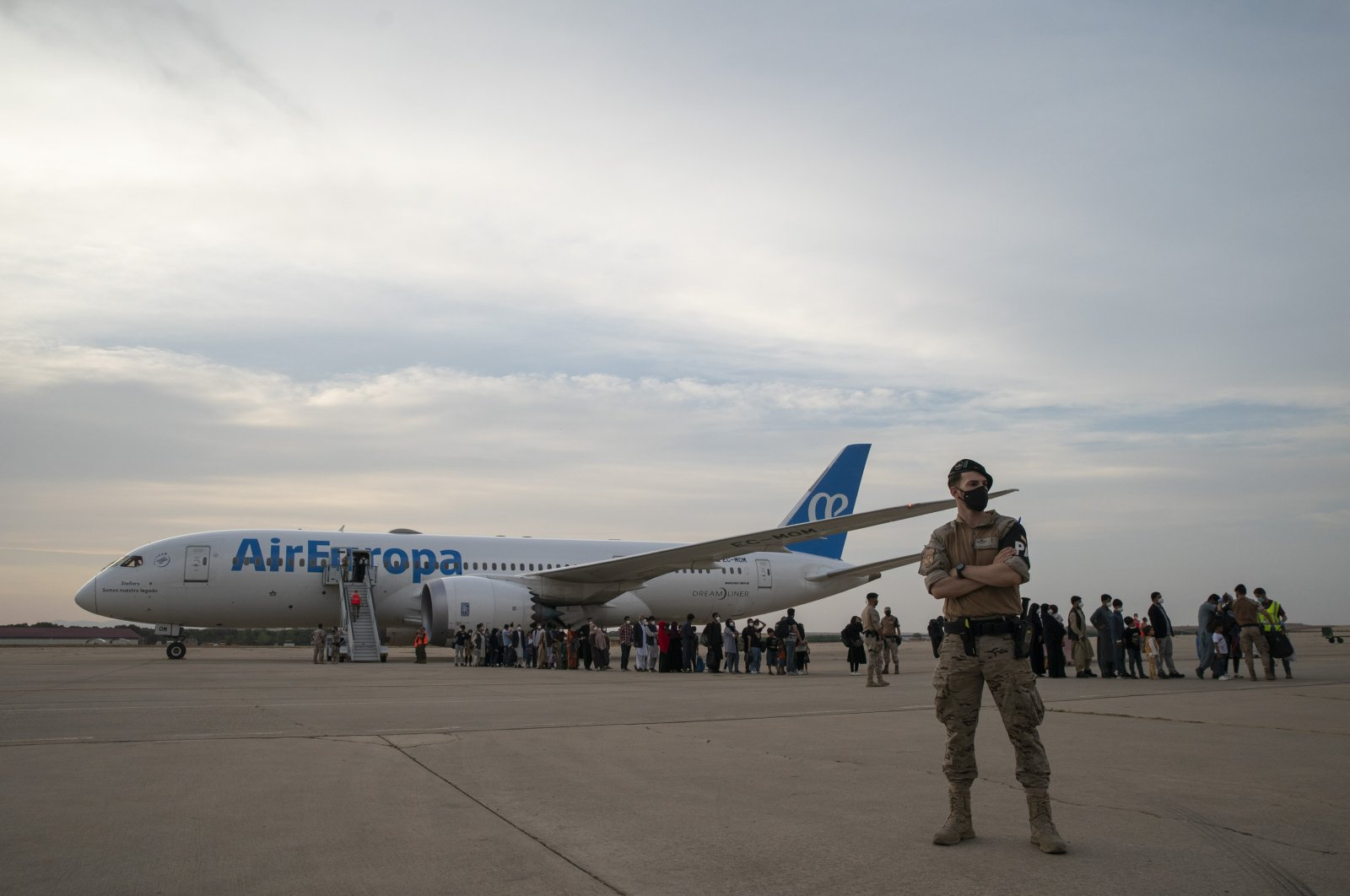 Afghans who were transported from Afghanistan, walk after disembarking a plane, at the Torrejon military base as part of the evacuation process in Madrid, Spain, Aug. 24, 2021. (AP Photo)