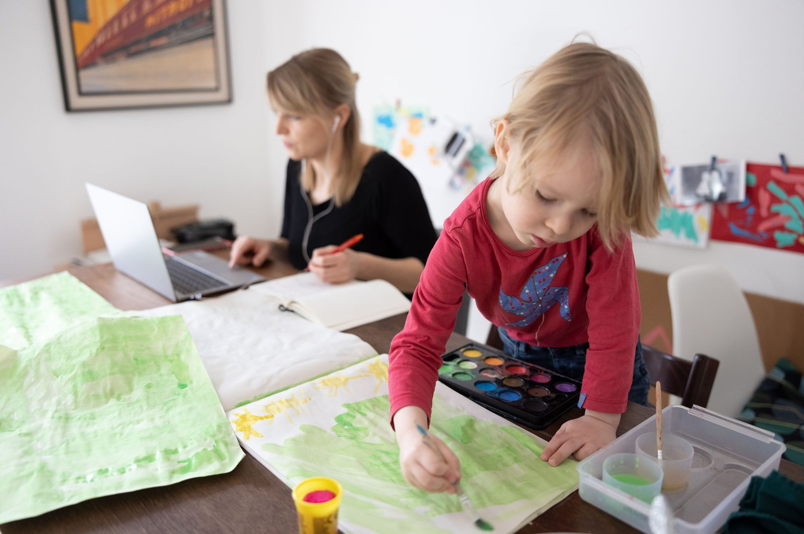 A woman worksand attends a digital conference at home while her son paints beside her,during the second wave of COVID-19pandemicin Zehlendorf district of Berlin, Germany, Feb. 18, 2021. (Getty Images)