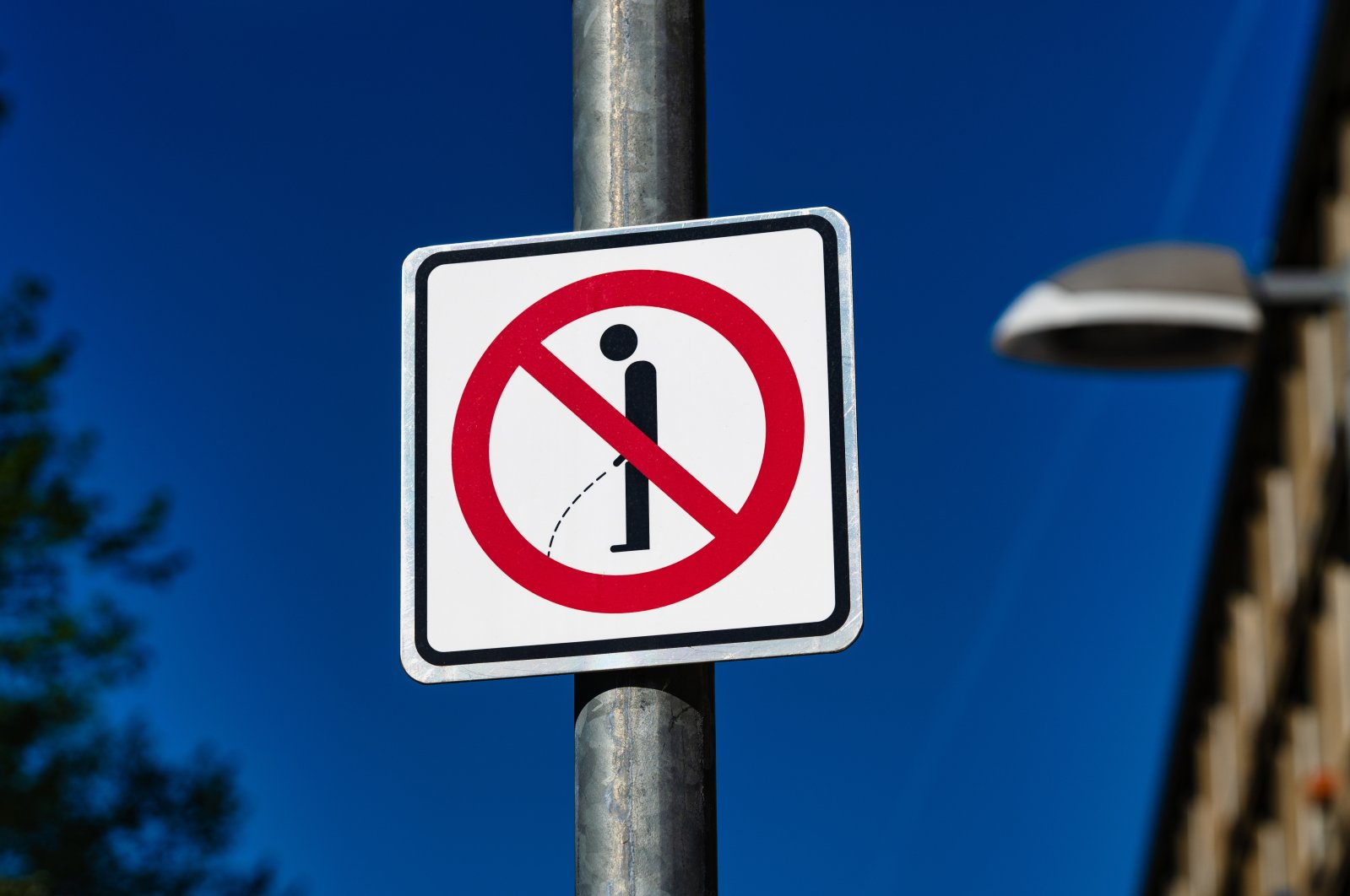 A sign reminding passersby to not pee in public.