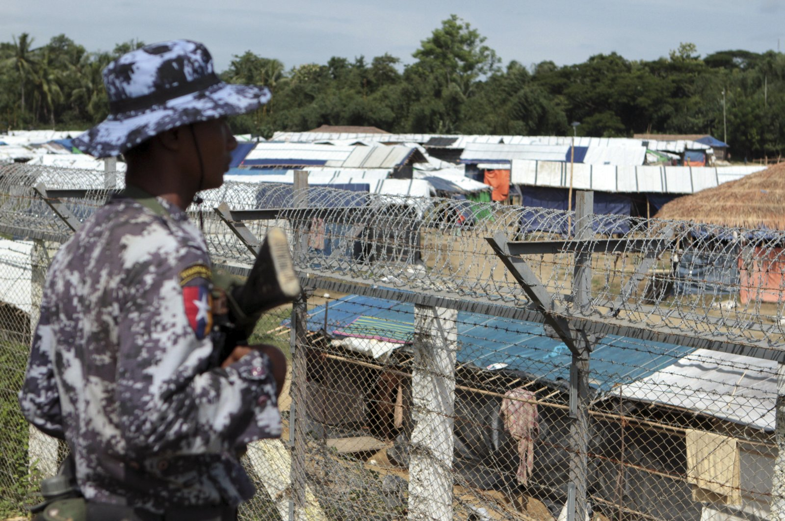 A Myanmar border guard stands to provide security near a fence at a no-man's land between Myanmar and Bangladesh, near Taungpyolatyar village, Maung Daw, northern Rakhine State, Myanmar, June 29, 2018. (AP Photo)