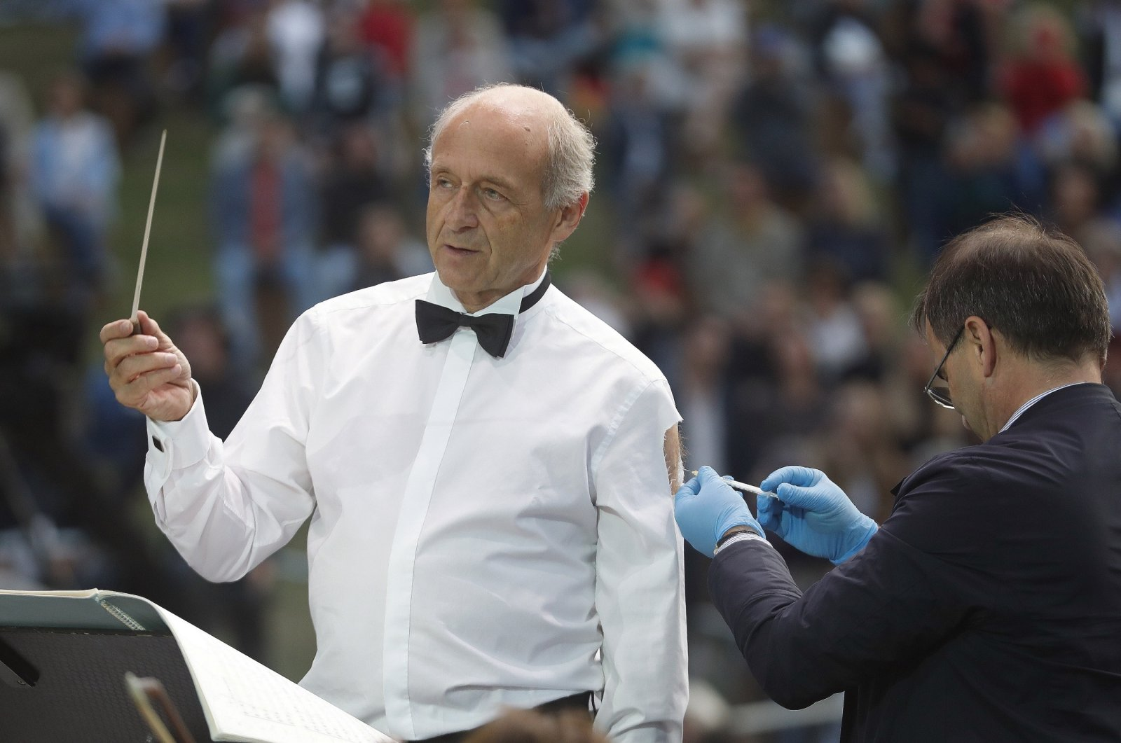 Ivan Fischer, the founder of the Budapest Festival Orchestra, receives his third dose of the COVID-19 vaccine as he conducts the orchestra, during their free concert in Budapest, Hungary, Aug. 25, 2021. (AP Photo)