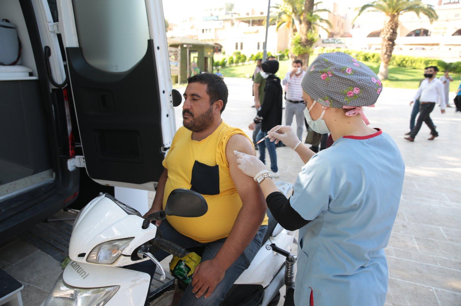 A man sits on his motorcycle while a nurse vaccinates him, in Şanlıurfa, southeastern Turkey, Aug. 27, 2021. (AA PHOTO)