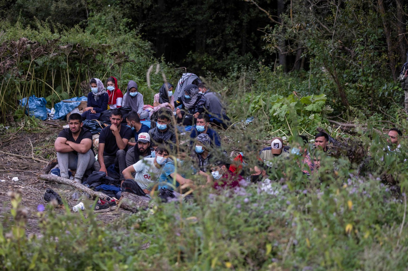 Migrants believed to be from Afghanistan sit on the ground in the small village of Usnarz Gorny near Bialystok, northeastern Poland, located close to the border with Belarus, Aug. 20, 2021. (AFP Photo)