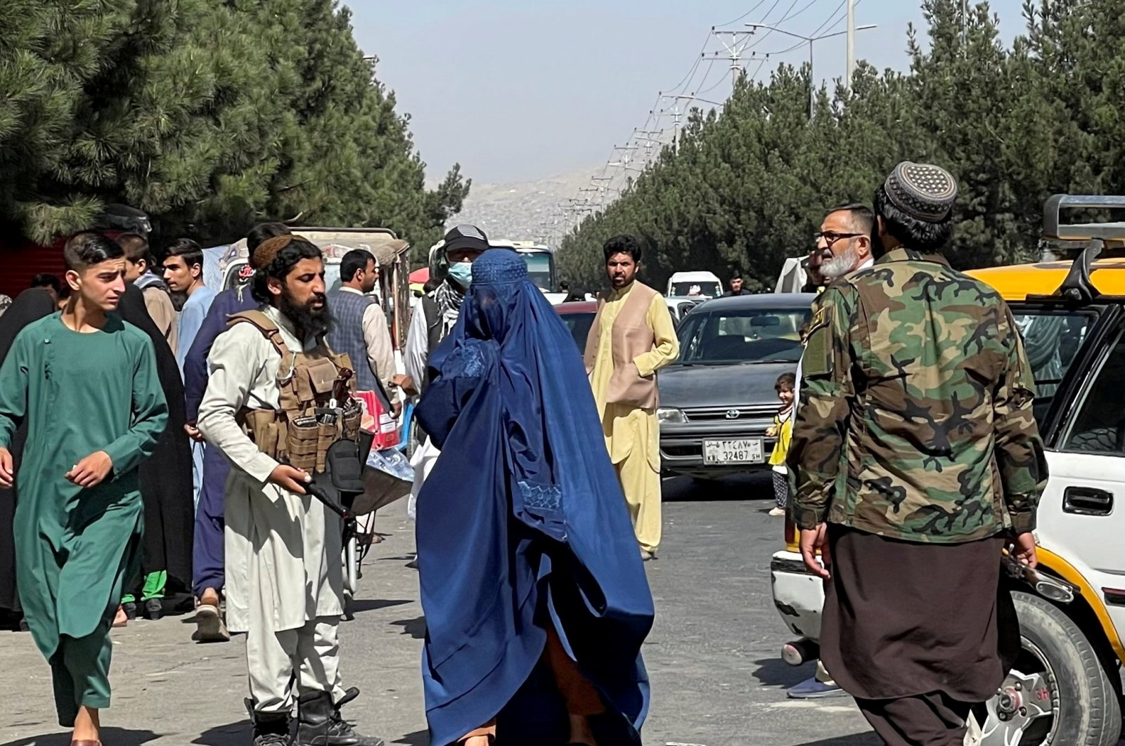 Taliban forces block the roads around the airport, while a woman wearing a burqa passes by, in Kabul, Afghanistan, Aug. 27, 2021. (Reuters Photo)