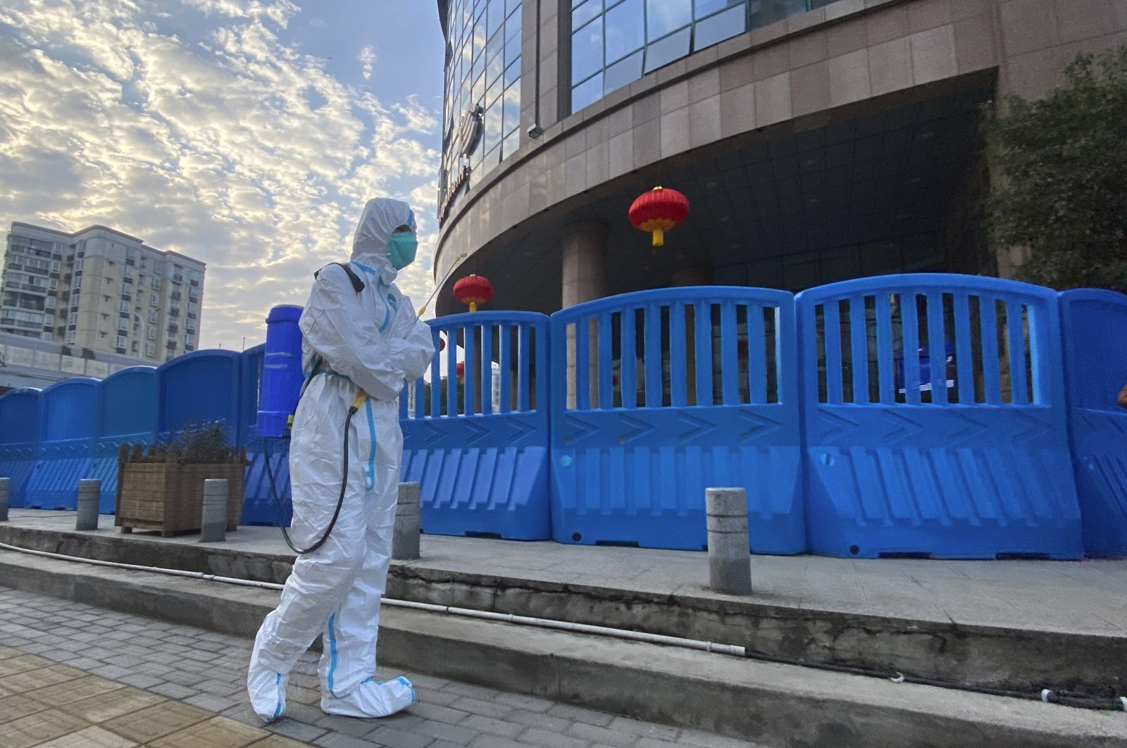 A worker in protective overalls and carrying disinfecting equipment walks outside the Wuhan Central Hospital where Li Wenliang, the whistleblower doctor who sounded the alarm and was reprimanded by local police for it in the early days of Wuhan's pandemic, worked in Wuhan in central China. (AP File Photo)