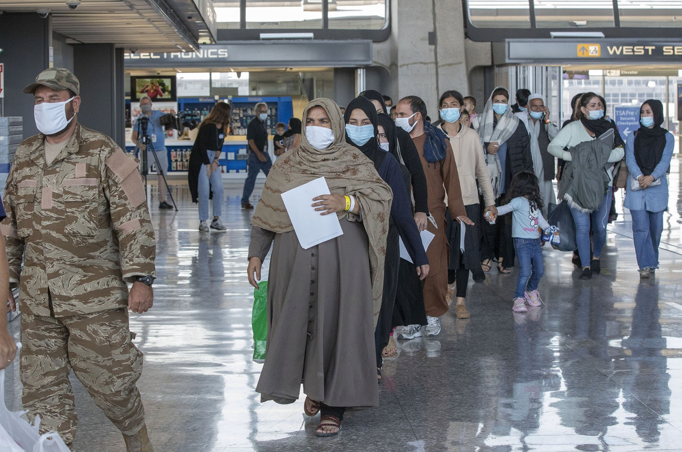 Families evacuated from Kabul, Afghanistan, walk through the terminal to board a bus after they arrived at Washington Dulles International Airport, in Chantilly, Virginia, U.S., Aug. 28, 2021. (AP Photo)