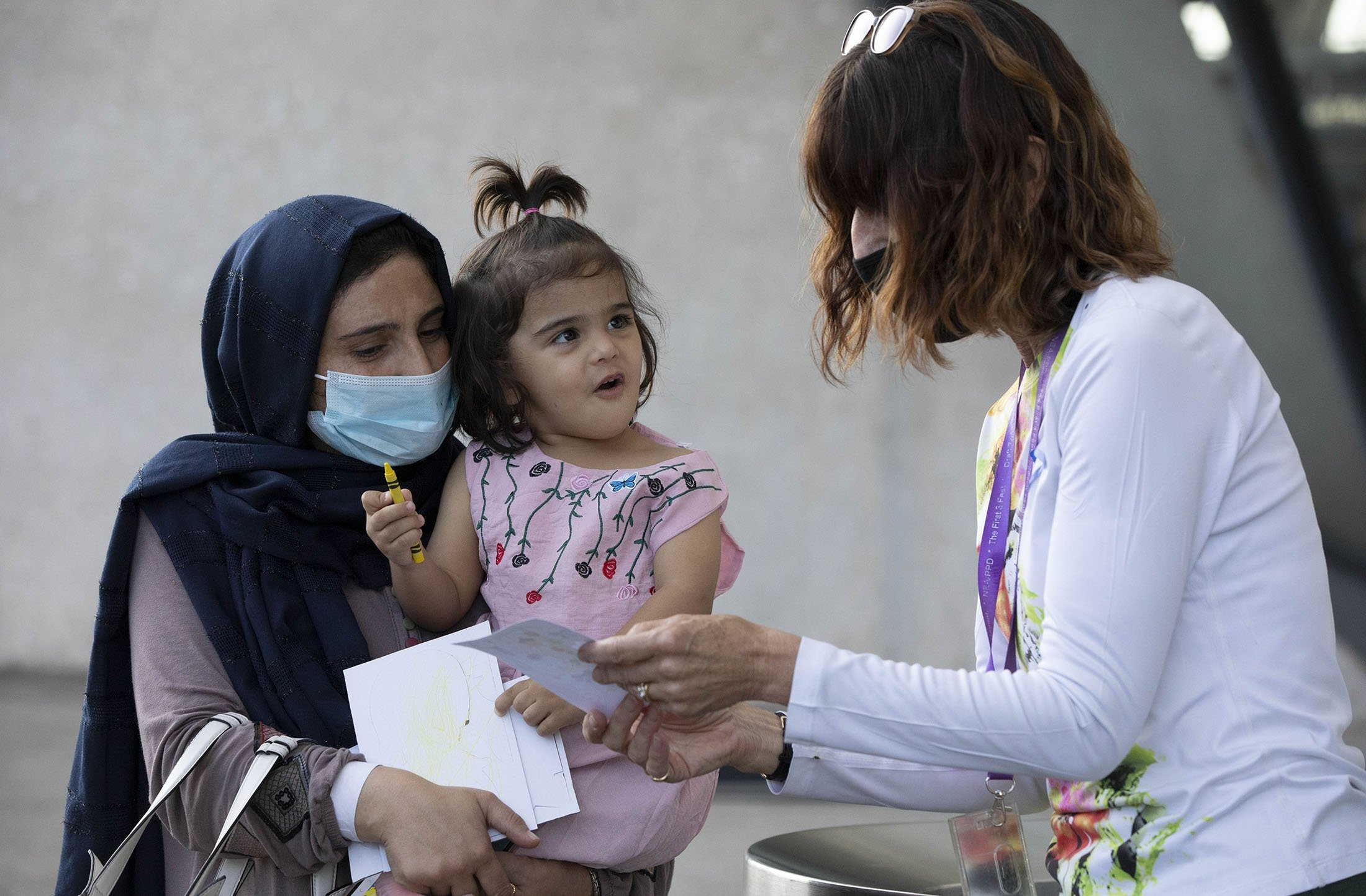 A volunteer interacts with a child evacuated from Kabul, Afghanistan at Washington Dulles International Airport, in Chantilly, Virginia, U.S., Aug. 28, 2021. (AP Photo)