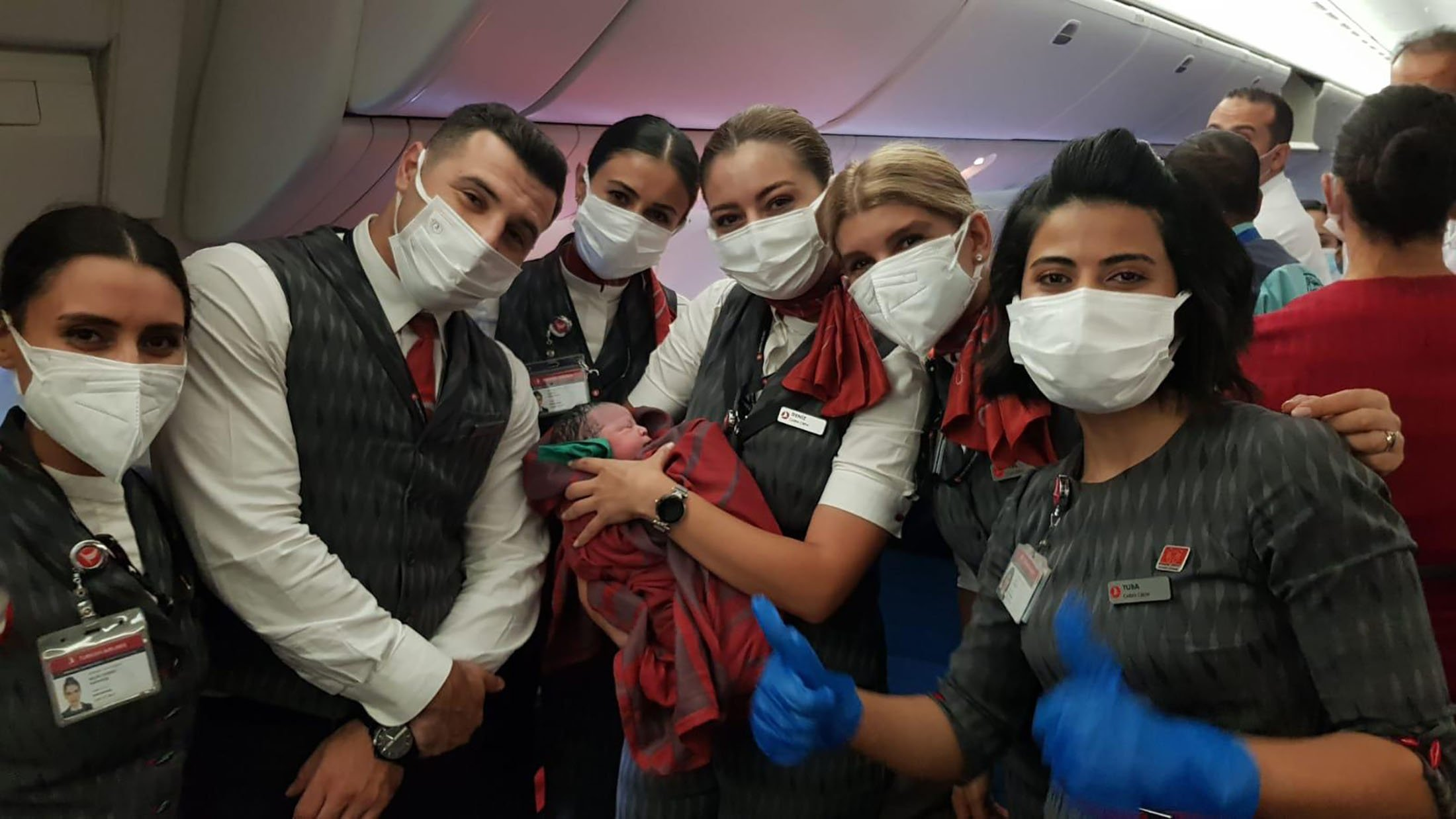 Turkish Airlines crew members pose with newly born Afghan baby girl Havva, which translates as Eve in English, during a flight between Dubai and Birmingham, U.K., Aug. 28, 2021. (Turkish Airlines via AP)