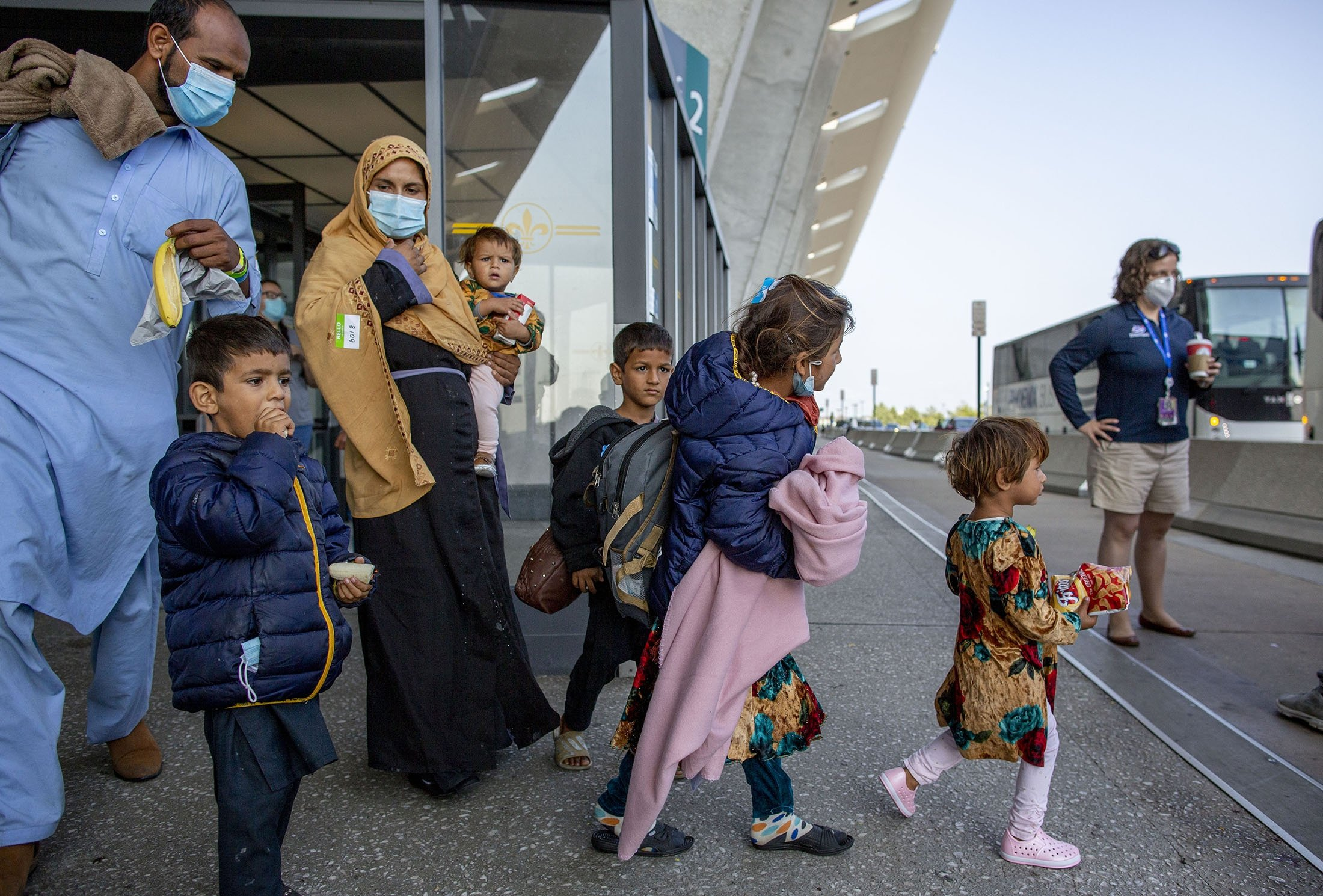 Families evacuated from Kabul, Afghanistan, walk to board a bus after they arrived at Washington Dulles International Airport, in Chantilly, Virginia, U.S., Aug. 28, 2021. (AP Photo)