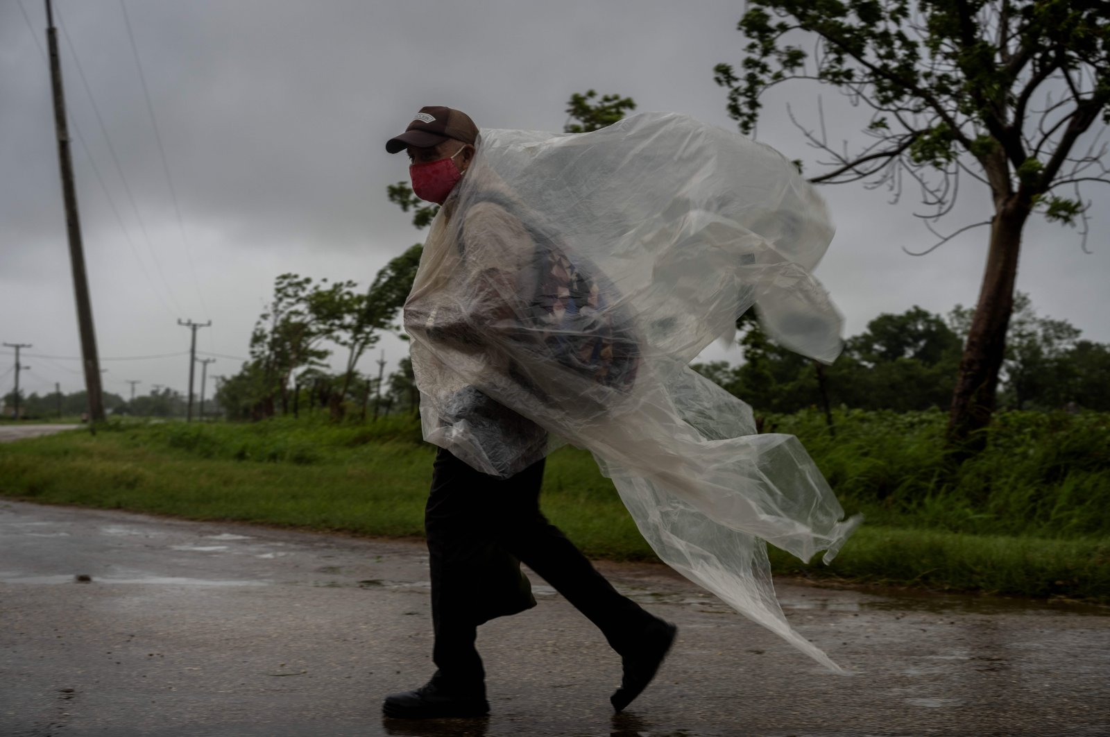 A man, wearing a makeshift poncho to protect himself from the rains of Hurricane Ida, walks on a road leading to Batabano, in the Mayabeque province, Cuba, Aug. 27, 2021. (AP Photo)