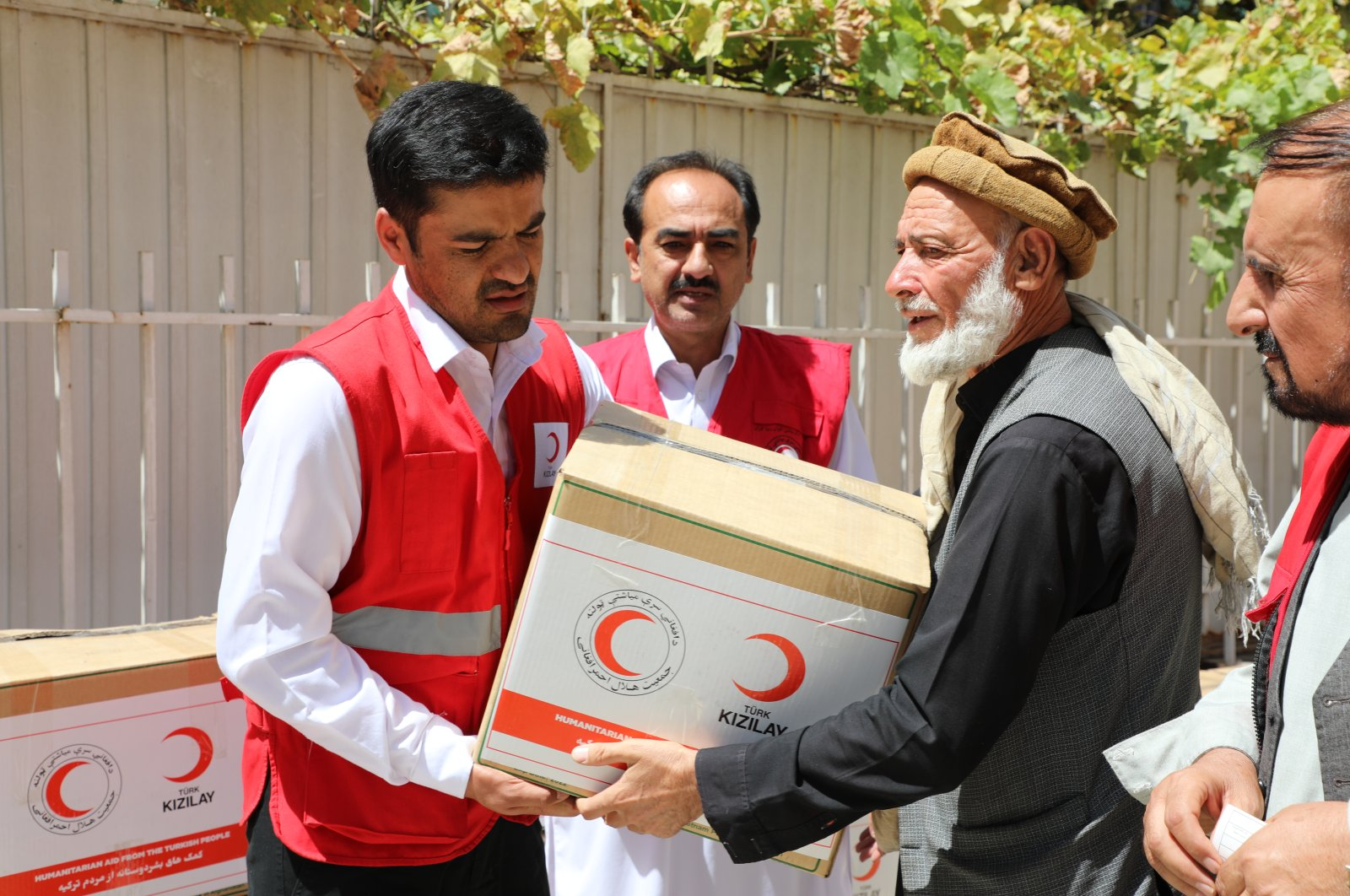 A Turkish Red Crescent worker distributes a food package to an old Afghan man, Kabul, Afghanistan, Aug. 28, 2021. (AA Photo)