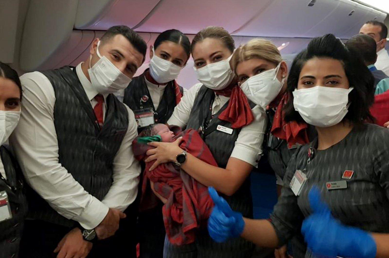 Turkish Airlines crew members hold newborn Havva during an evacuation flight from Kabul to Birmingham, Aug. 28, 2021. (AA Photo)