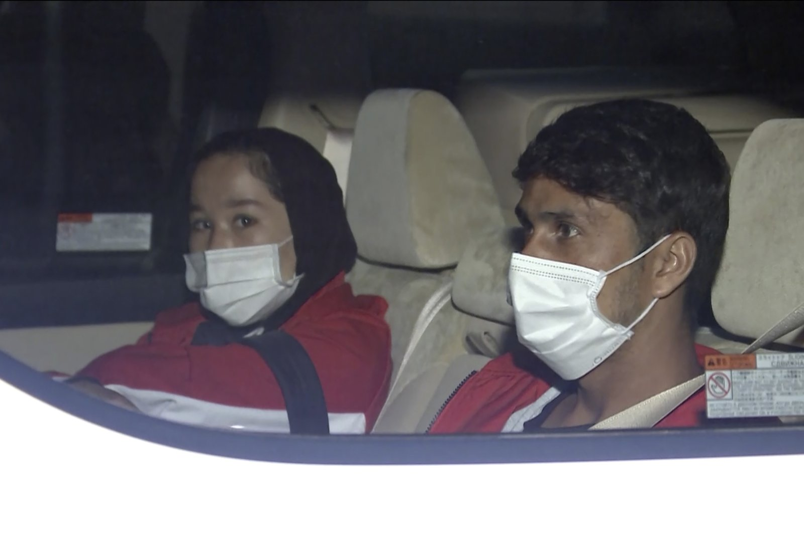 In this image made from a video, Afghan athletes Zakia Khudadadi (L) and Hossain Rasouli arrive at Haneda airport, Tokyo, Japan, Saturday, Aug. 28, 2021. (AP Photo)