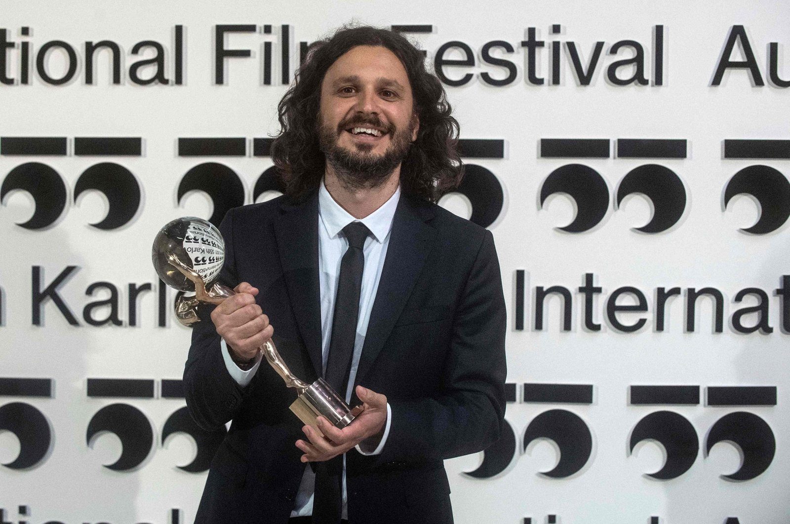 """Serbian director Stefan Arsenijevic poses with the Crystal Globe for Best Film for his film """"As Far As I Can Walk"""" at the 55th Karlovy Vary International Film Festival (KVIFF) in Karlovy Vary, Czech Republic, Aug. 28, 2021. (AFP Photo)"""