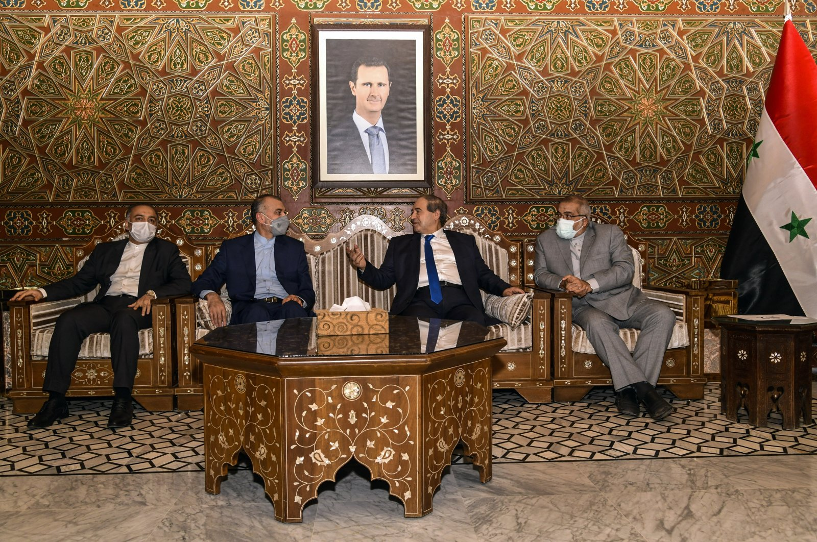 Syria's Foreign Minister Faisal Mekdad, (2-R), receives Iran's new Foreign Minister Hossein Amir-Abdollahian, (2-L), in Damascus, Syria, Sunday, Aug. 29, 2021. (SANA via AP)