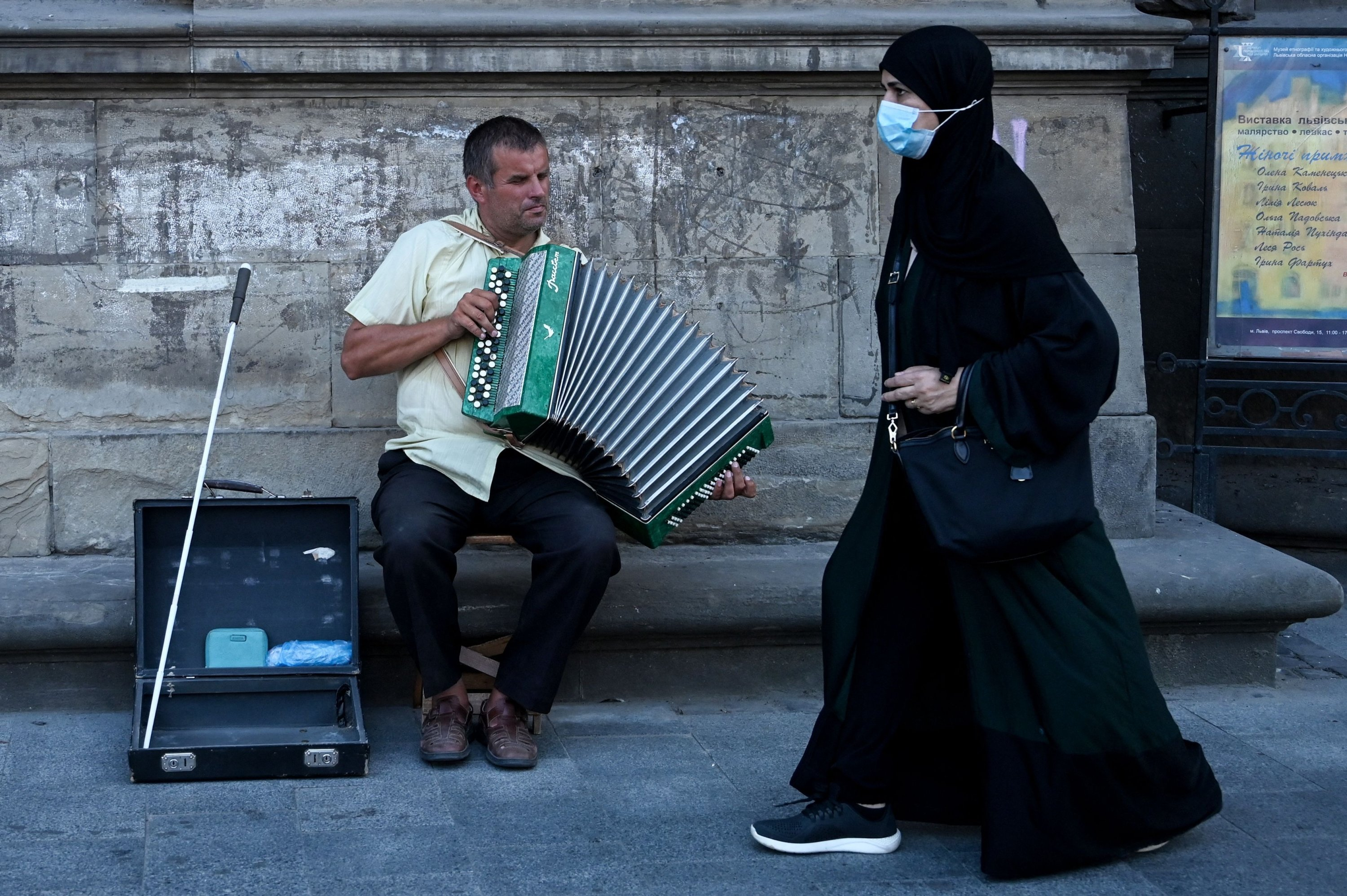 A woman from the Middle East walks past a street musician in Lviv, Ukraine, Aug. 14, 2021. (AFP Photo)