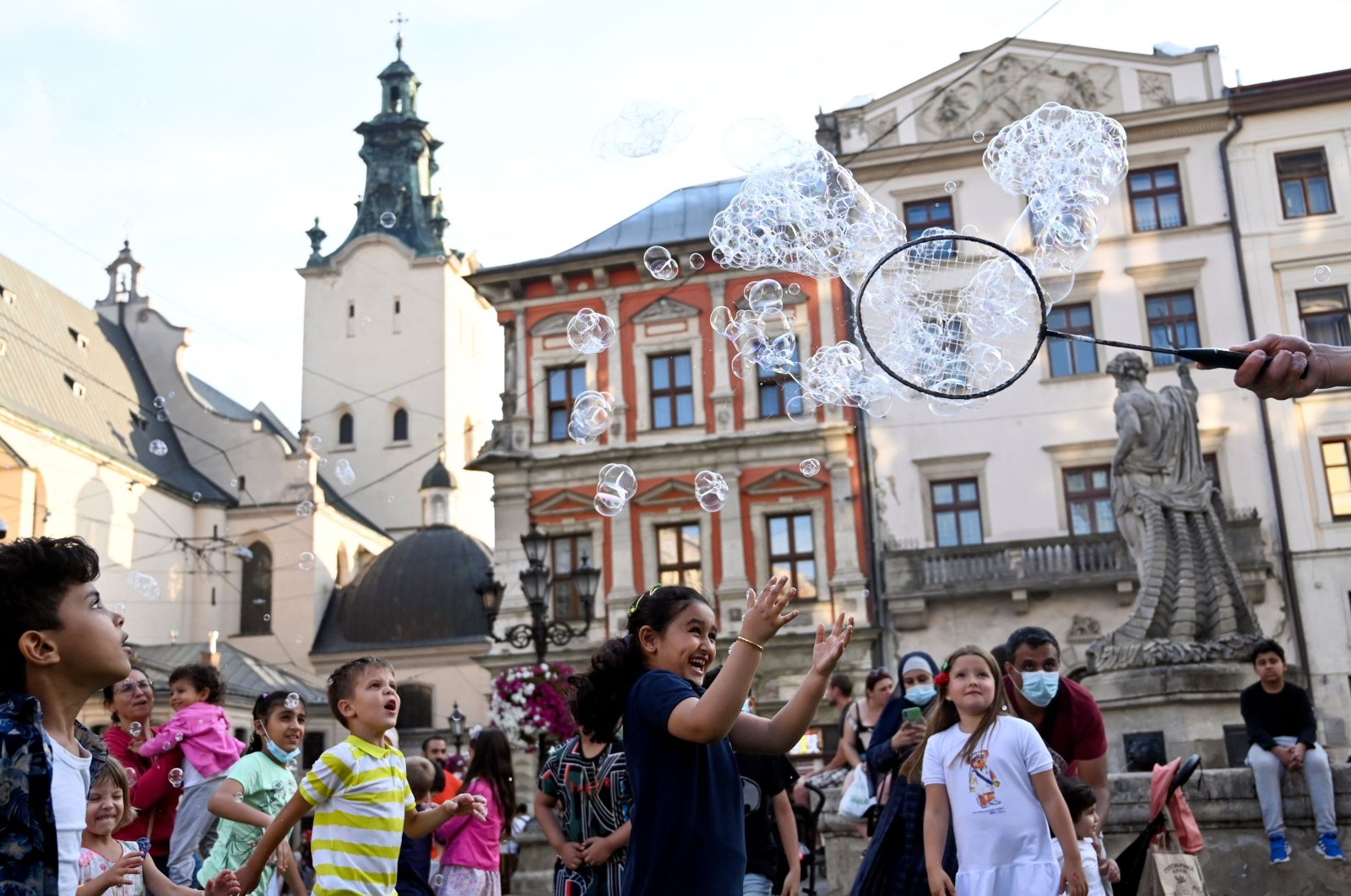 Middle Eastern tourists play with bubbles in Lviv, Ukraine, Aug. 14, 2021. (AFP Photo)