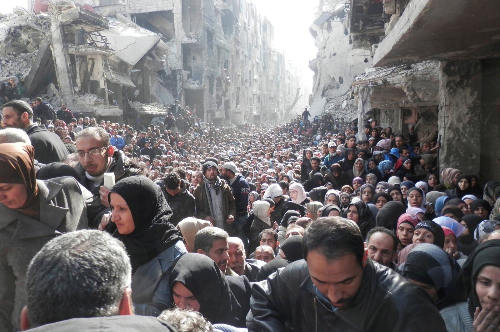Residents wait to receive food aid distributed by the U.N. Relief and Works Agency (UNRWA) at the besieged al-Yarmouk camp, south of Damascus, Syria, Jan. 31, 2014. (Reuters Photo)