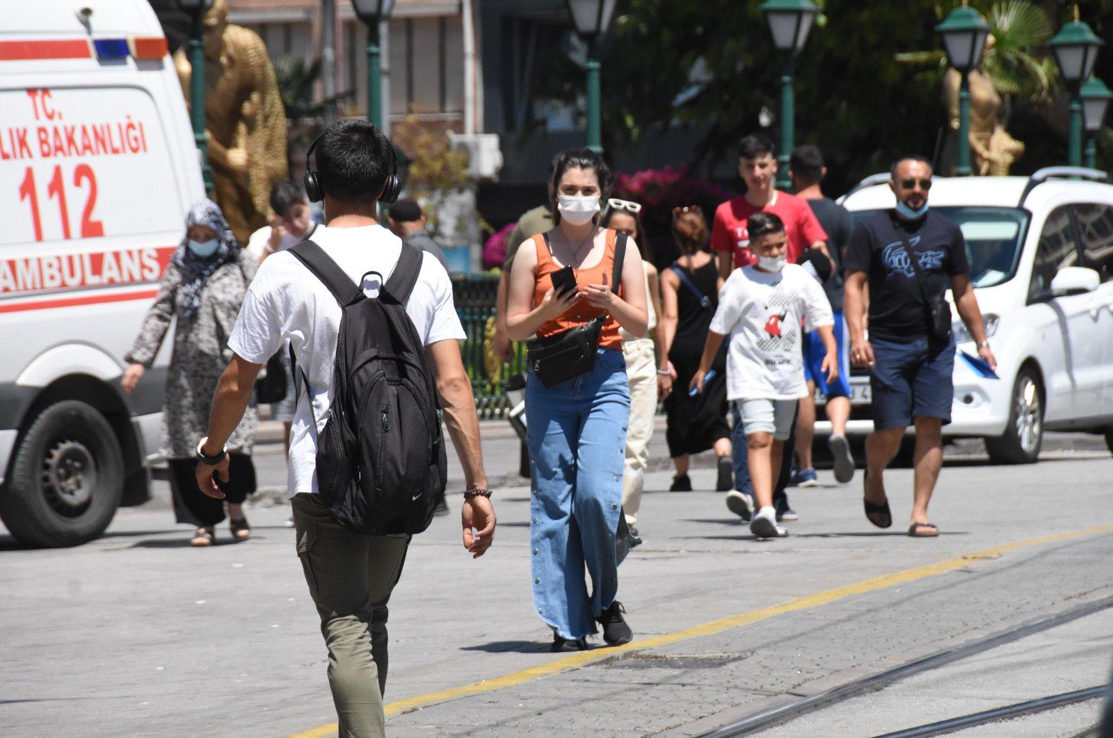 People wearing protective masks walk on a street, in Eskişehir, central Turkey, Aug. 28, 2021. (DHA Photo)