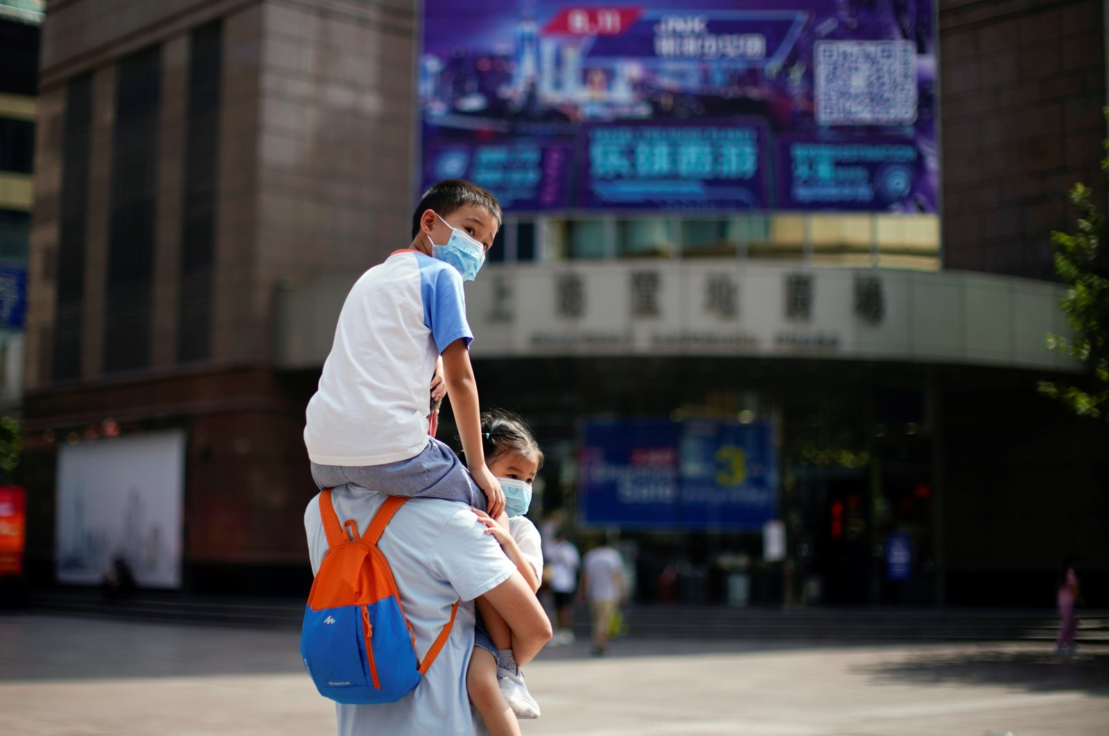 A man carries two children, all wearing protective face masks following new cases of COVID-19, on a street in Shanghai, China, Aug. 25, 2021. (Reuters Photo)