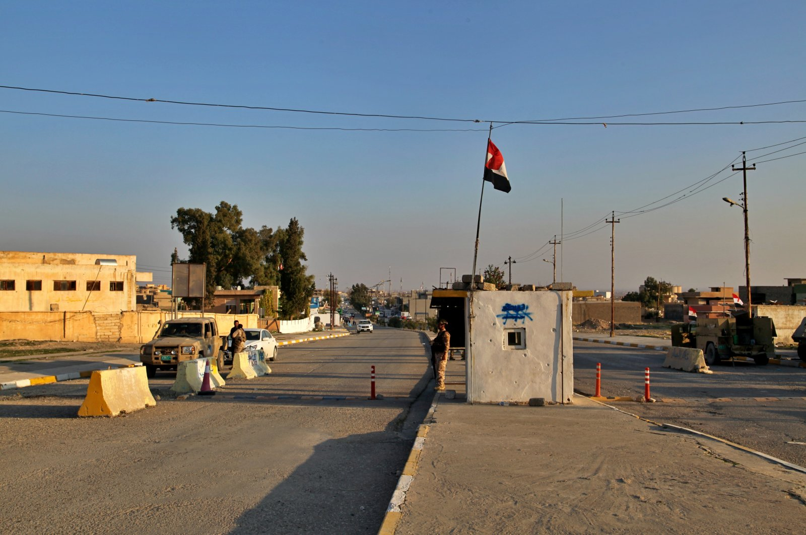 Iraqi soldiers stand guard under a national flag at a checkpoint in the city of Sinjar, Iraq. Dec. 4, 2020. (AP File Photo)