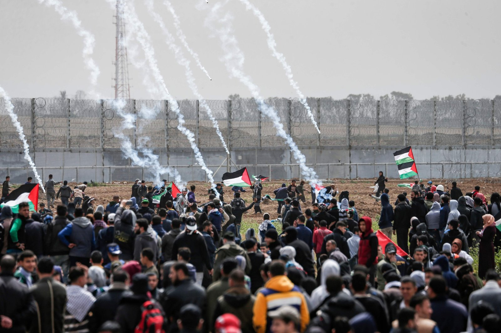 """Tear gas canisters fall amongst Palestinian protesters during a demonstration near the border with Israel as Palestinians mark the first anniversary of the """"March of Return"""" border protests in Malaka east of Gaza City, Palestine, on March 30, 2019. (AFP Photo)"""