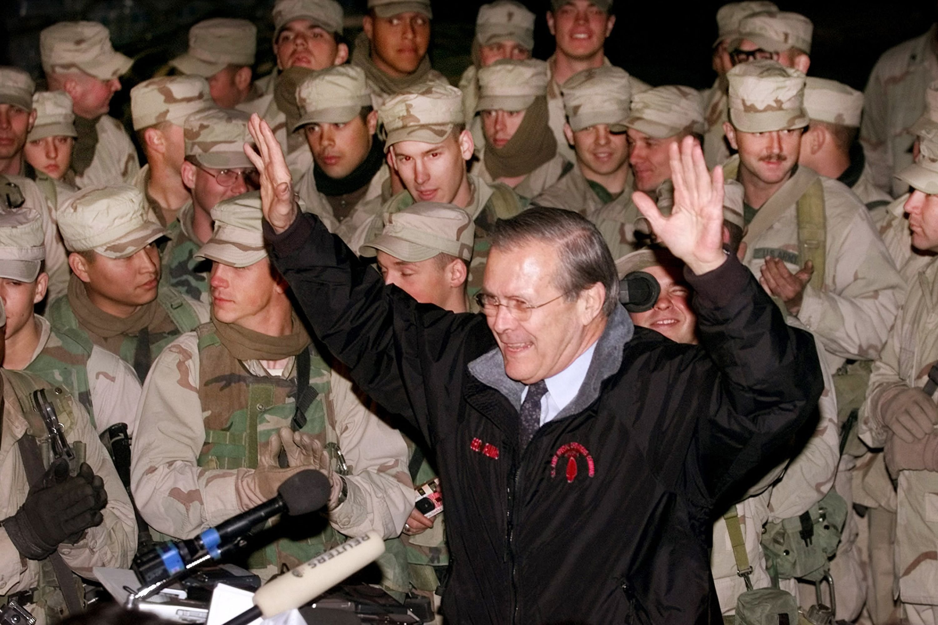 US Secretary of Defense Donald Rumsfeld raising his arms as he concludes his meeting with troops from 1st Battalion 87 at Bagram airfield, Afghanistan, December 18, 2001 (AFP photo)