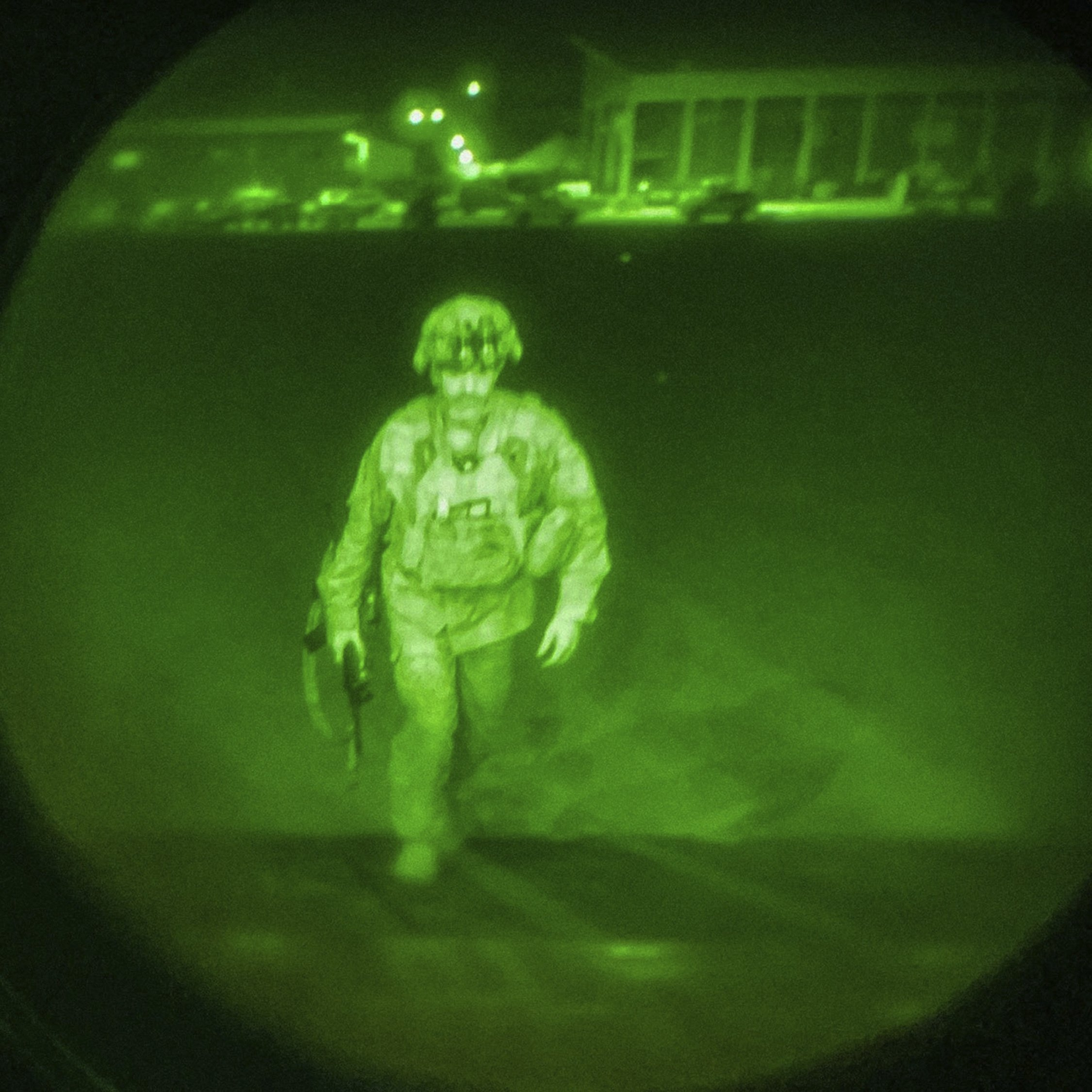 In this image made through a night vision scope and provided by U.S. Central Command, Maj. Gen. Chris Donahue, commander of the U.S. Army 82nd Airborne Division, XVIII Airborne Corps, boards a C-17 cargo plane at Hamid Karzai International Airport in Kabul, Afghanistan, Aug. 30, 2021, as the final American service member to depart Afghanistan. (U.S. Central Command via AP)
