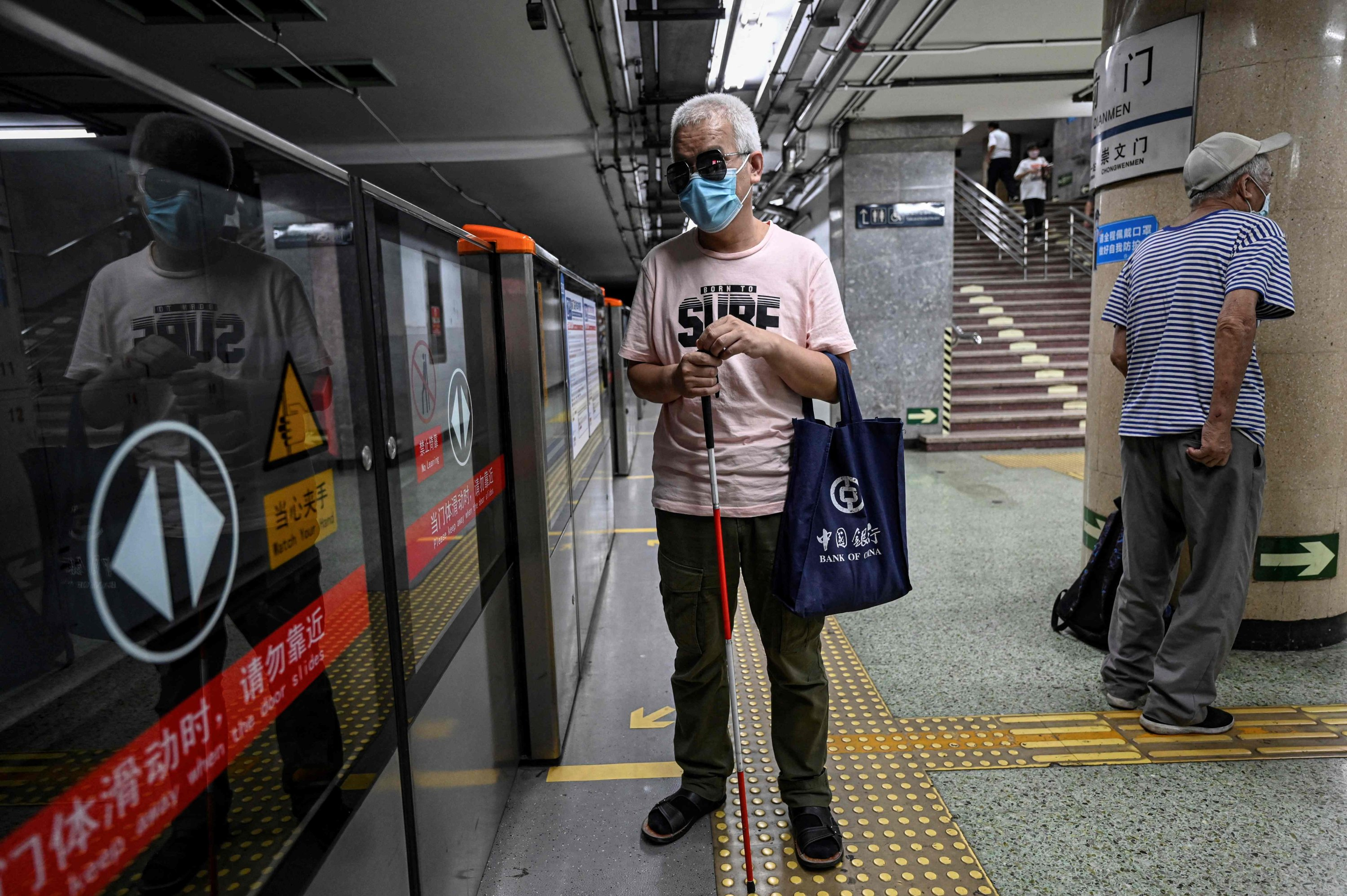Visually impaired massage therapist Zhang Xinsheng waits for a train at a subway station in Beijing, China, Aug. 7, 2021. (AFP Photo)
