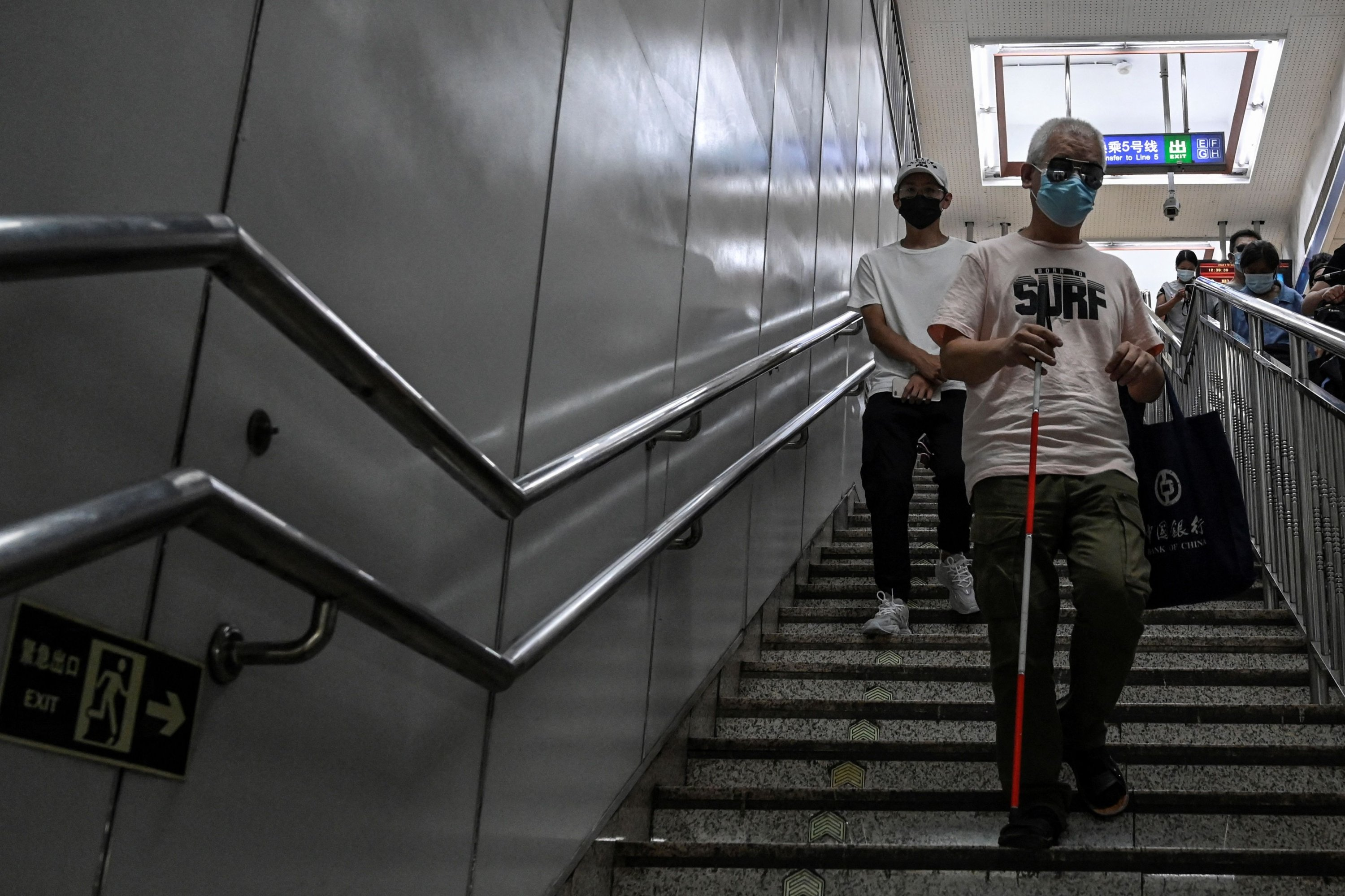 Visually impaired massage therapist Zhang Xinsheng walks down the stairs with his cane at a subway station in Beijing, China, Aug. 7, 2021. (AFP Photo)