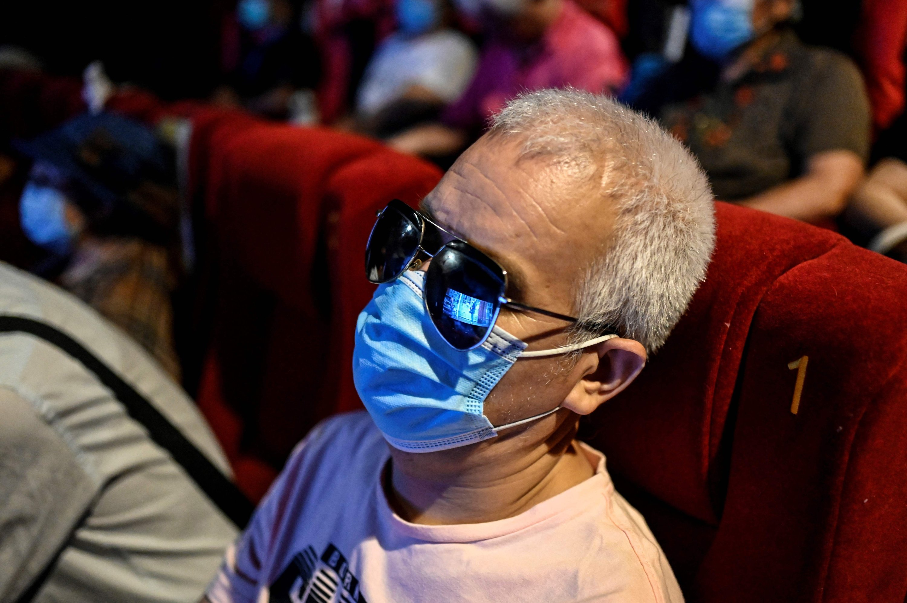 Visually impaired massage therapist Zhang Xinsheng listens to the film narrator during a screening at a cinema in Beijing, China, Aug. 7, 2021. (AFP Photo)
