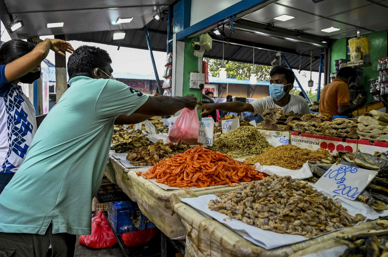 A vendor (R) sells dried fish at a market in Colombo on Aug. 28, 2021, after Sri Lanka extended a stringent COVID-19 curfew for another week after reporting its highest daily death toll of more than 200. (AFP Photo)
