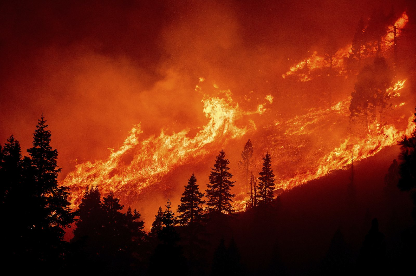 Flames from the Caldor Fire leap along a hillside above Christmas Valley, South Lake Tahoe, California, U.S., Aug. 30, 2021. (AP Photo)
