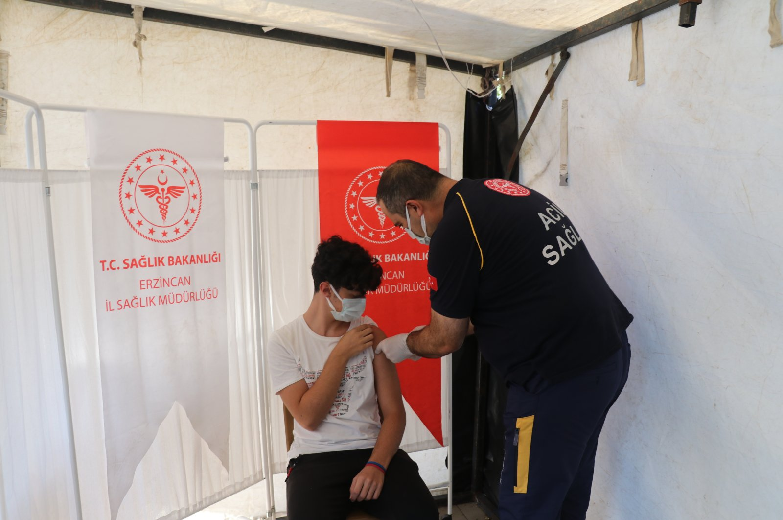 Erkan Hirik, head of local Directorate of Health, vaccinates his son Gün, in Erzincan, eastern Turkey, Aug. 28, 2021. (AA PHOTO)